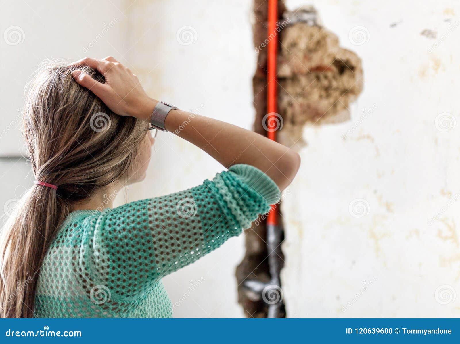 Kvinna som ser skada efter en läcka för vattenrör