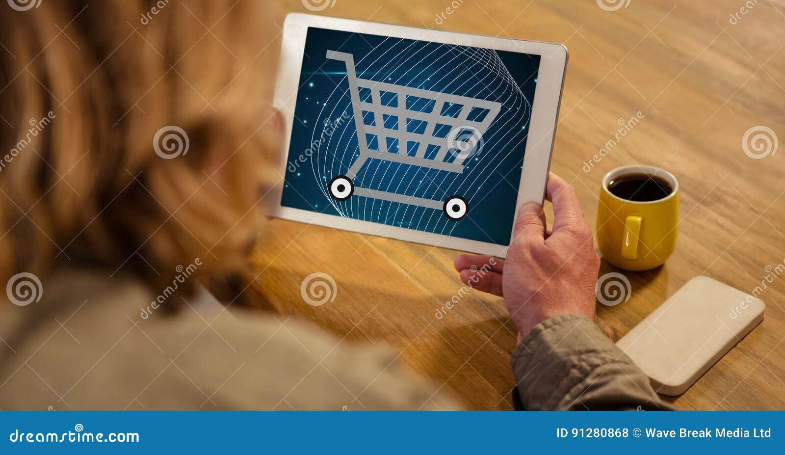 Kvinna som ser symbolen för shoppingvagn på minnestavlaPC