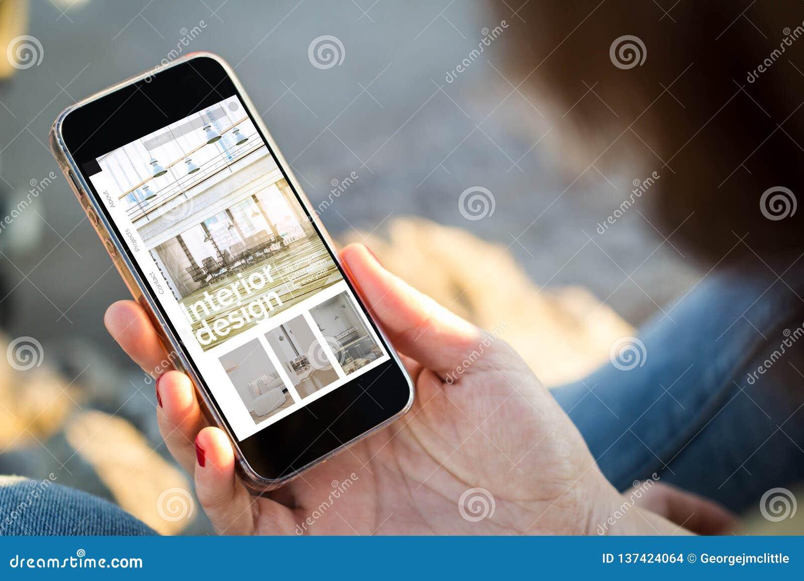 Kvinna som sitter i gatan som rymmer hennes smartphone som visar websiten för inredesign