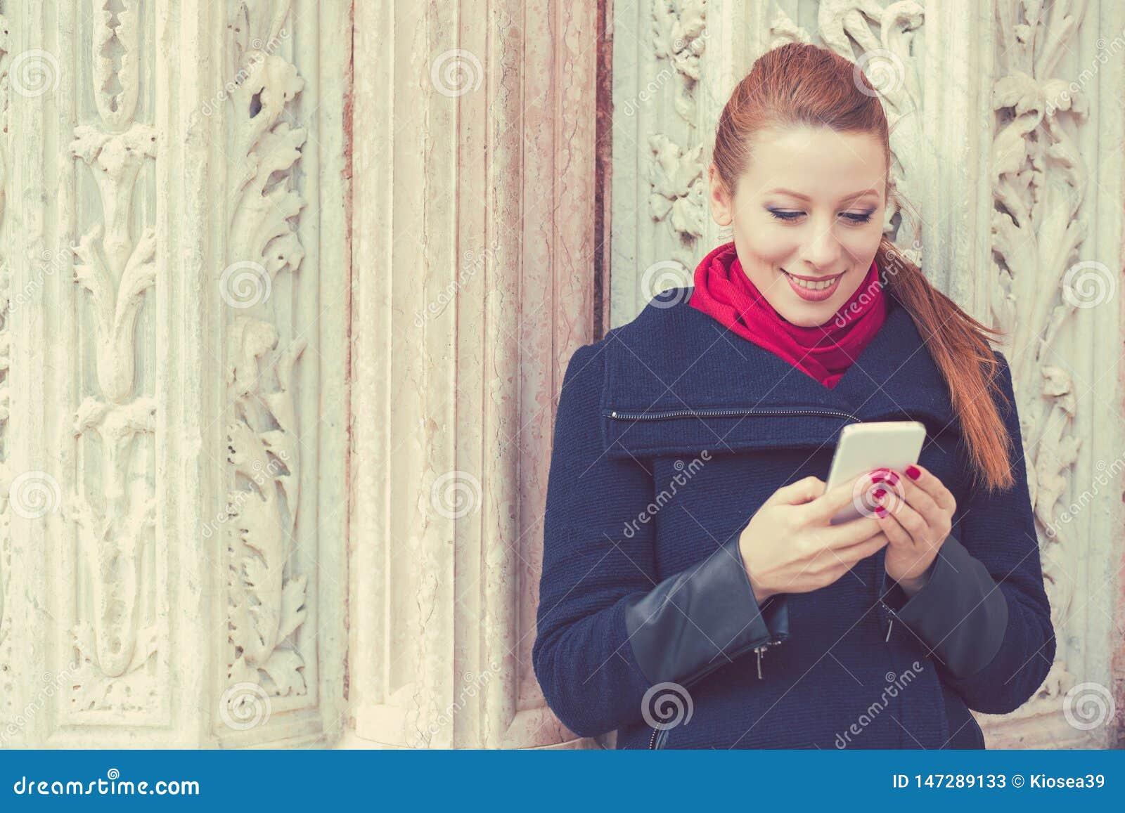 Kvinna som smsar p? en telefon