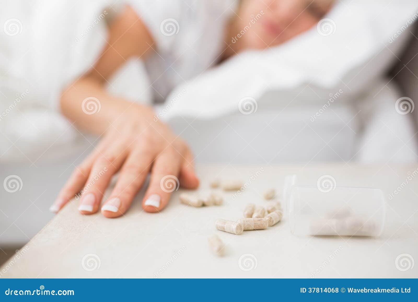 Kvinna som sover i säng med preventivpillerar i förgrund