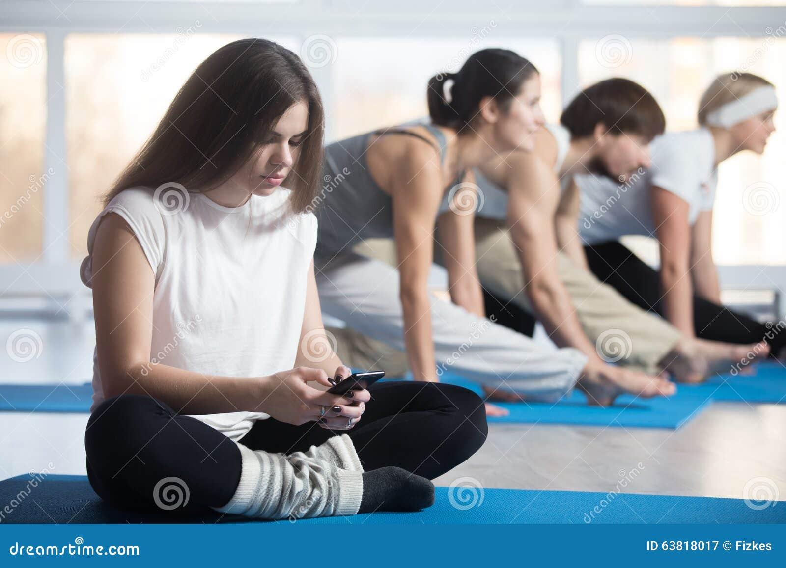 Kvinna som spelar med telefonen i stället för sportutbildning