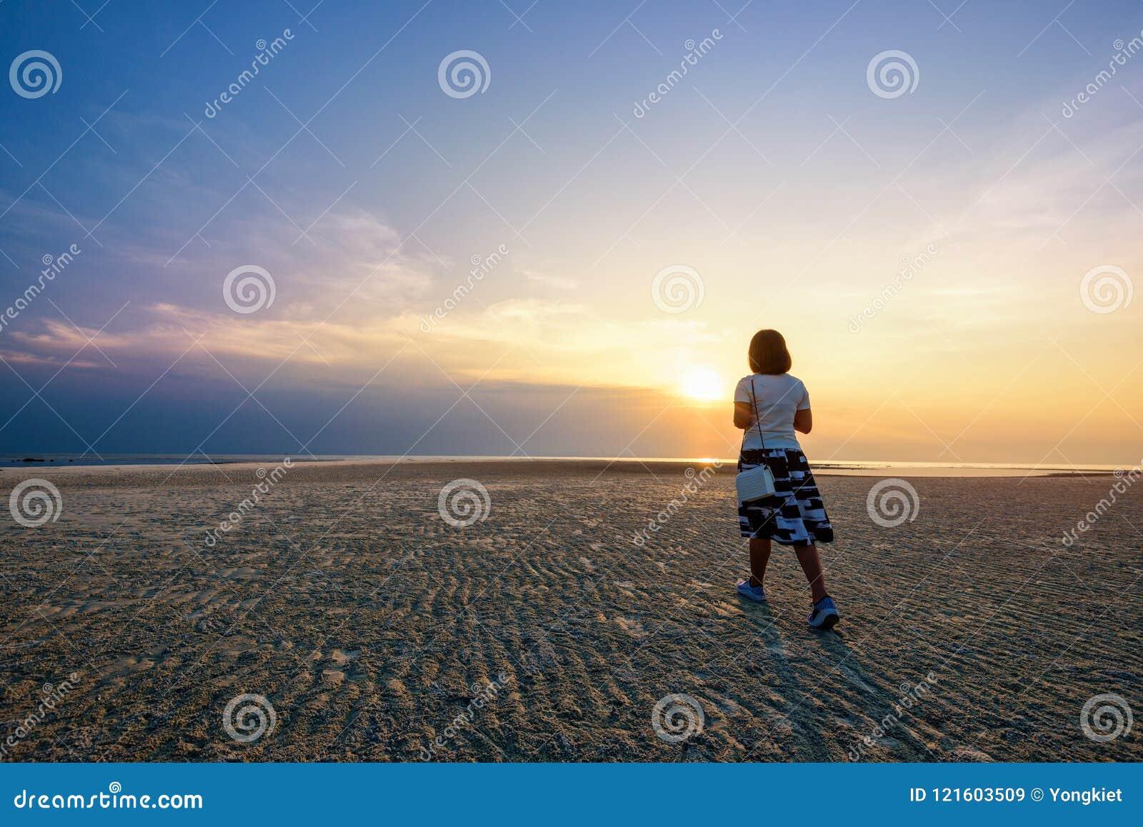 Kvinna som strosar på stranden på solnedgången