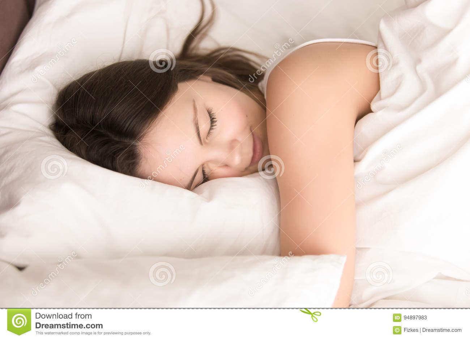 Kvinna som ta sig en tupplur, medan krama den mjuka kudden i säng