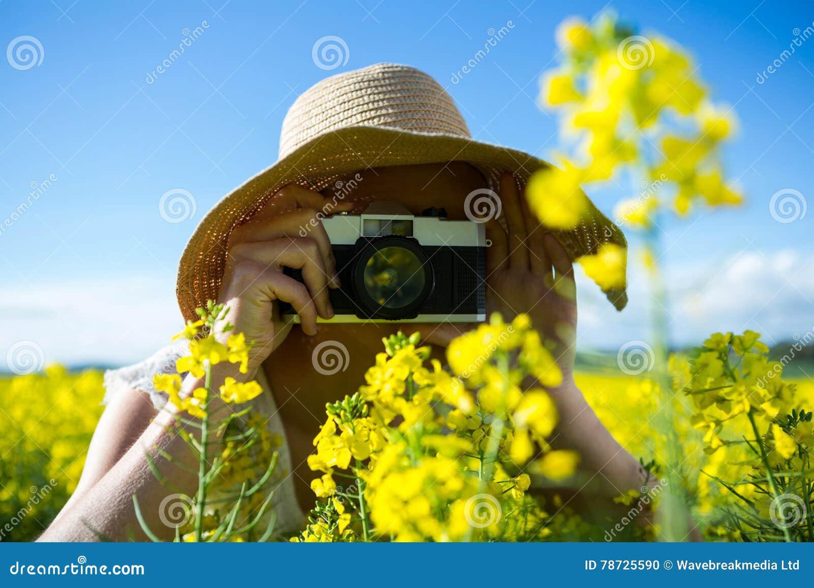 Kvinna som tar bilden från kamera i senapsgult fält