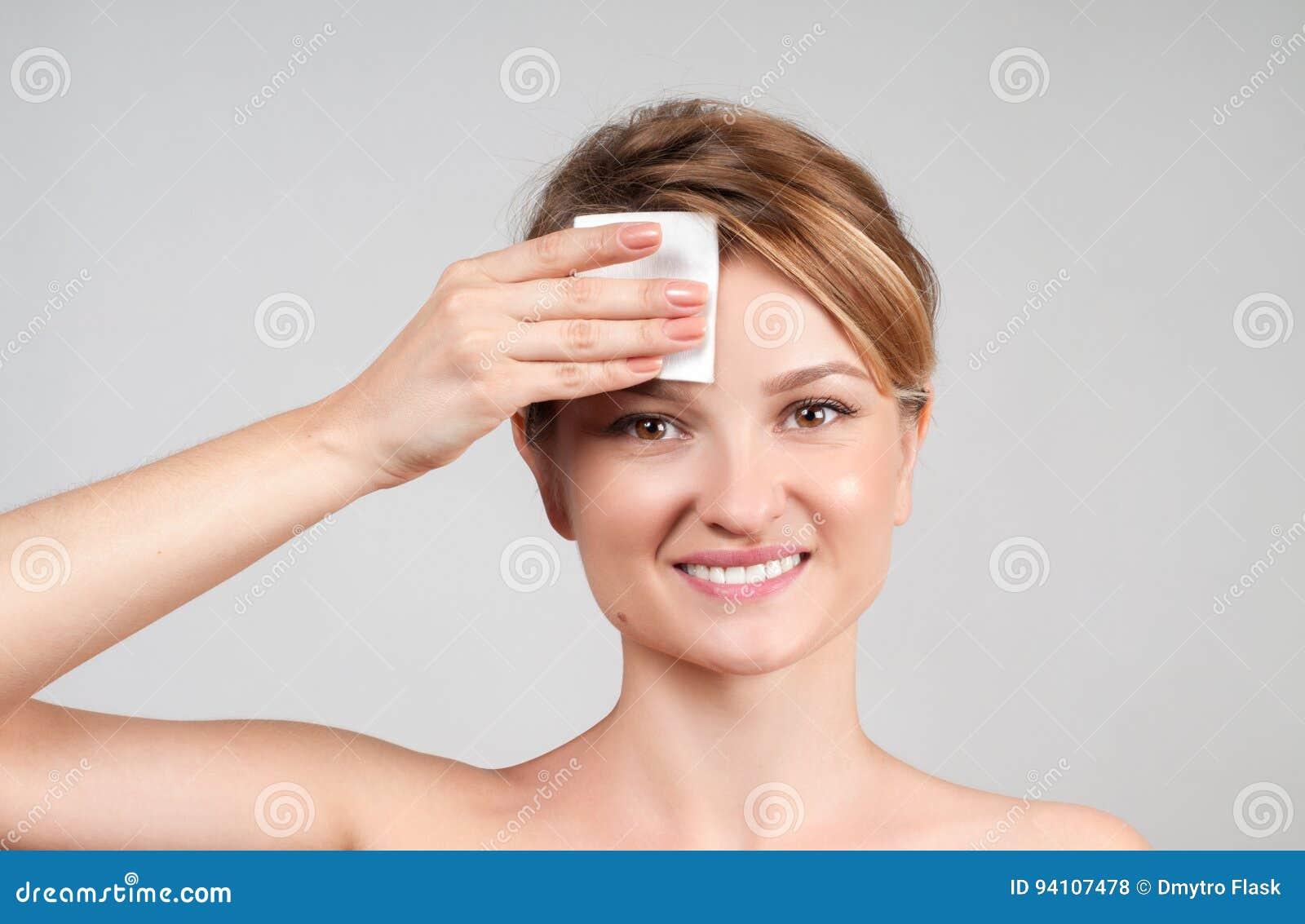 _ Kvinna som tar bort makeup med bomullsblocket