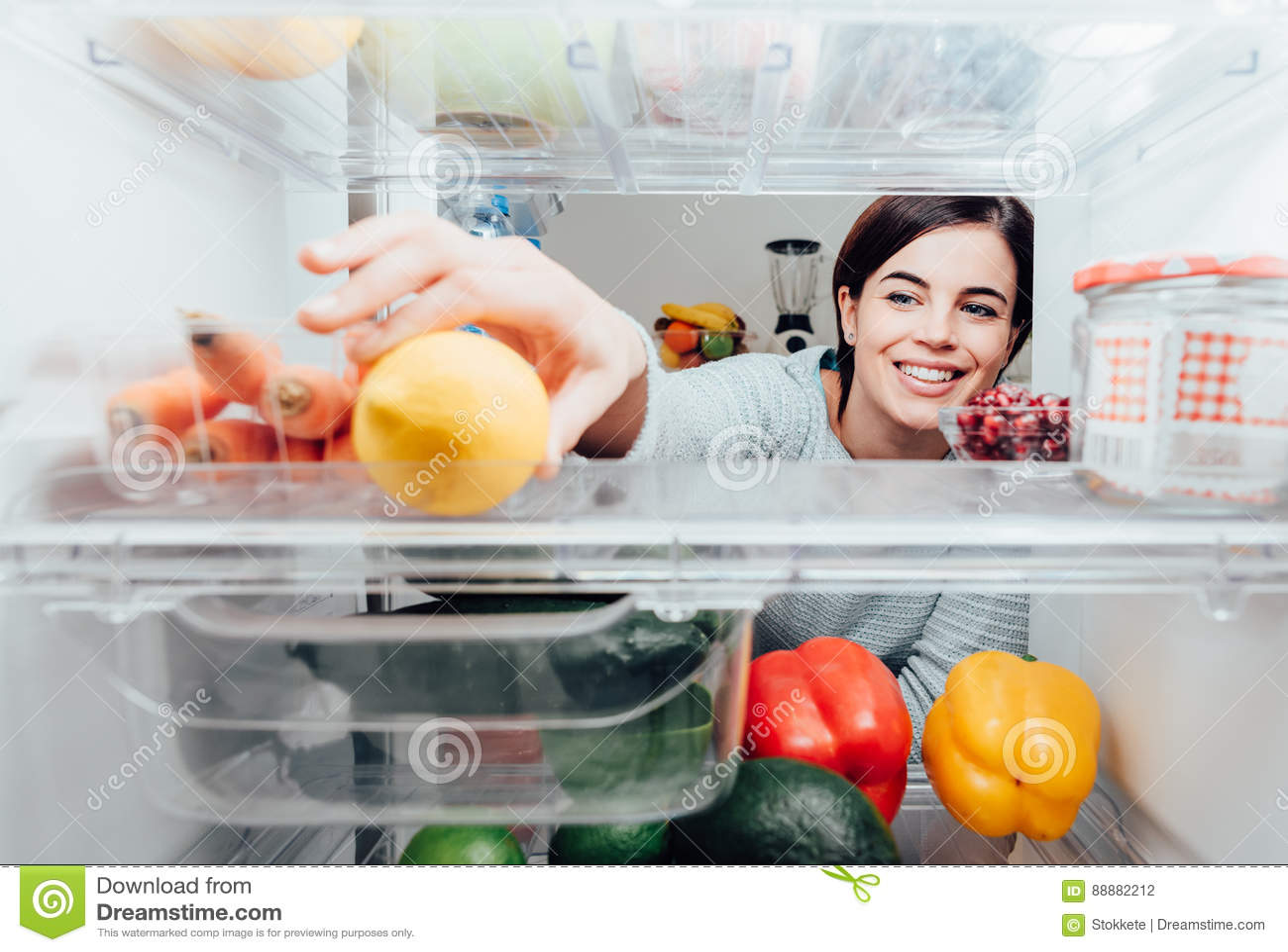Kvinna som tar en citron ut ur kylen