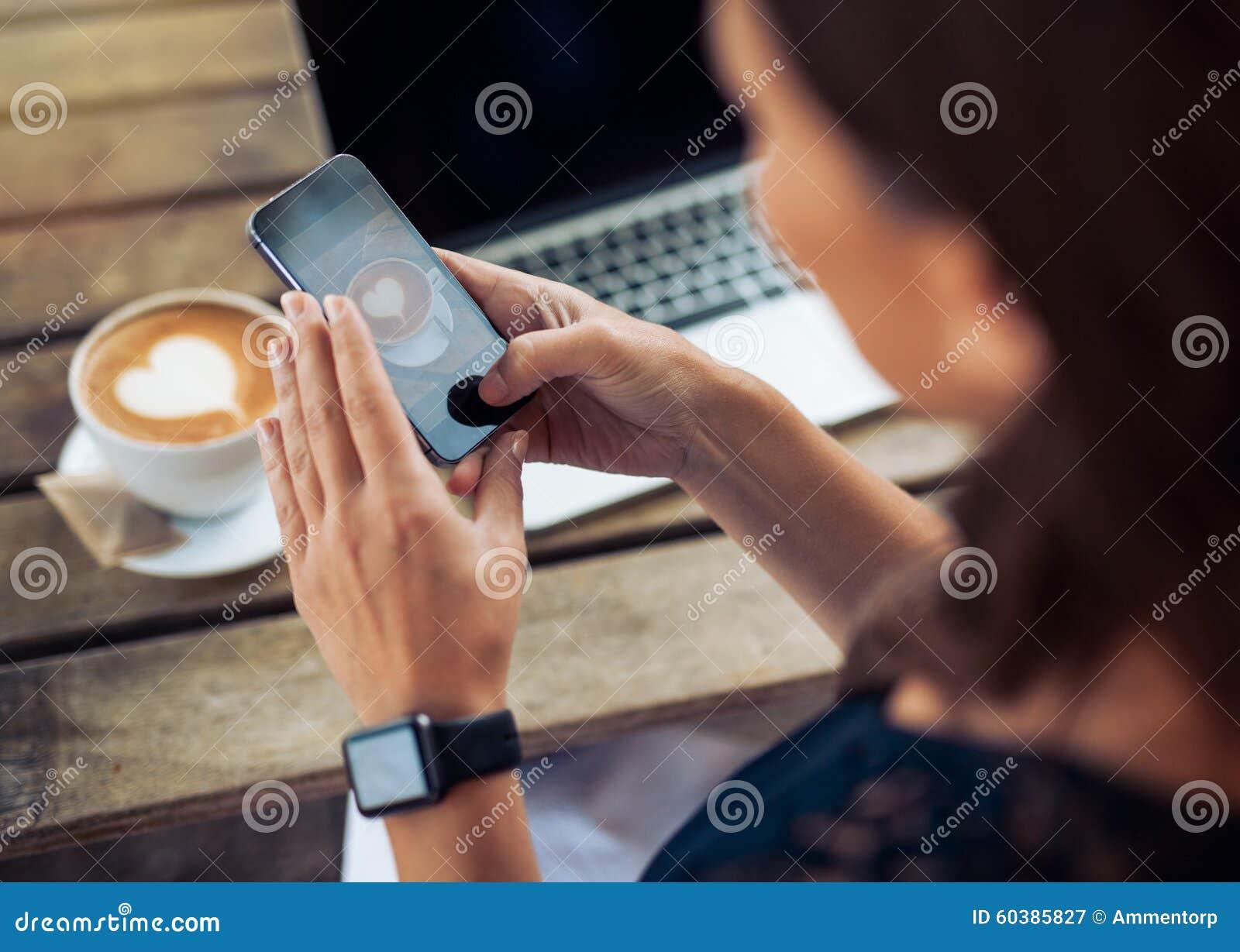 Kvinna som tar fotoet av kaffe med smartphonen