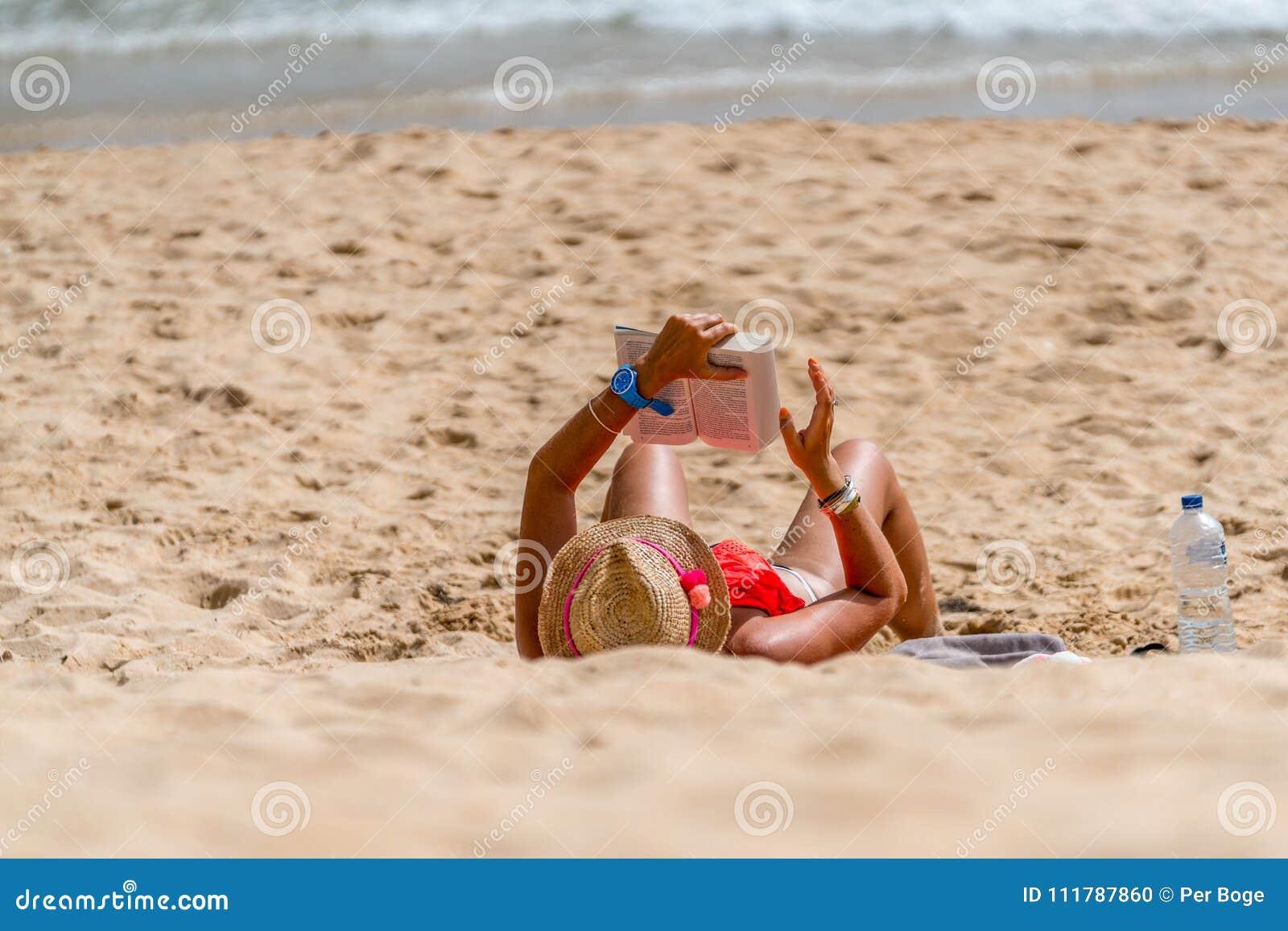 Kvinna som tillbaka ligger på henne på en strand som läser en bok