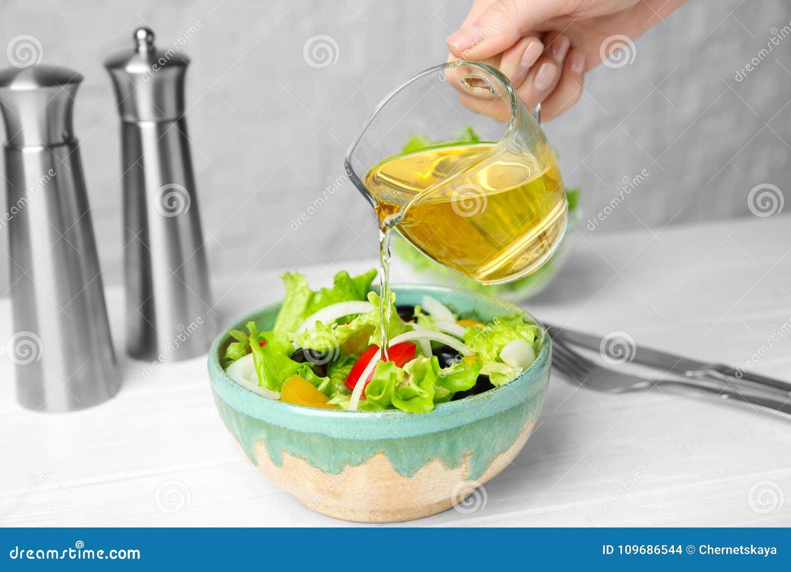 Kvinna som tillfogar smaklig äpplevinäger in i sallad