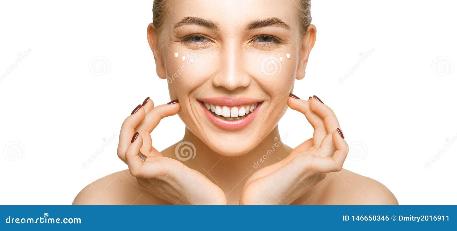 Kvinna som trycker på hennes framsida vid händer Applicera kräm på en perfekt slät mjuk hud