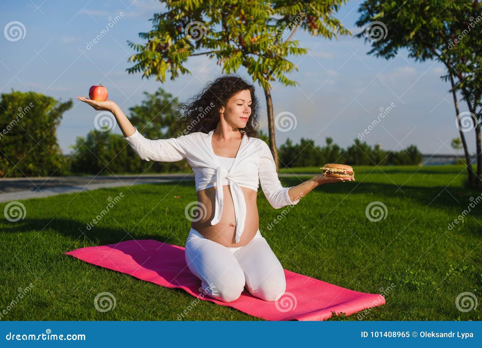 Kvinna som väljer mellan en hamburgare och ett äpple