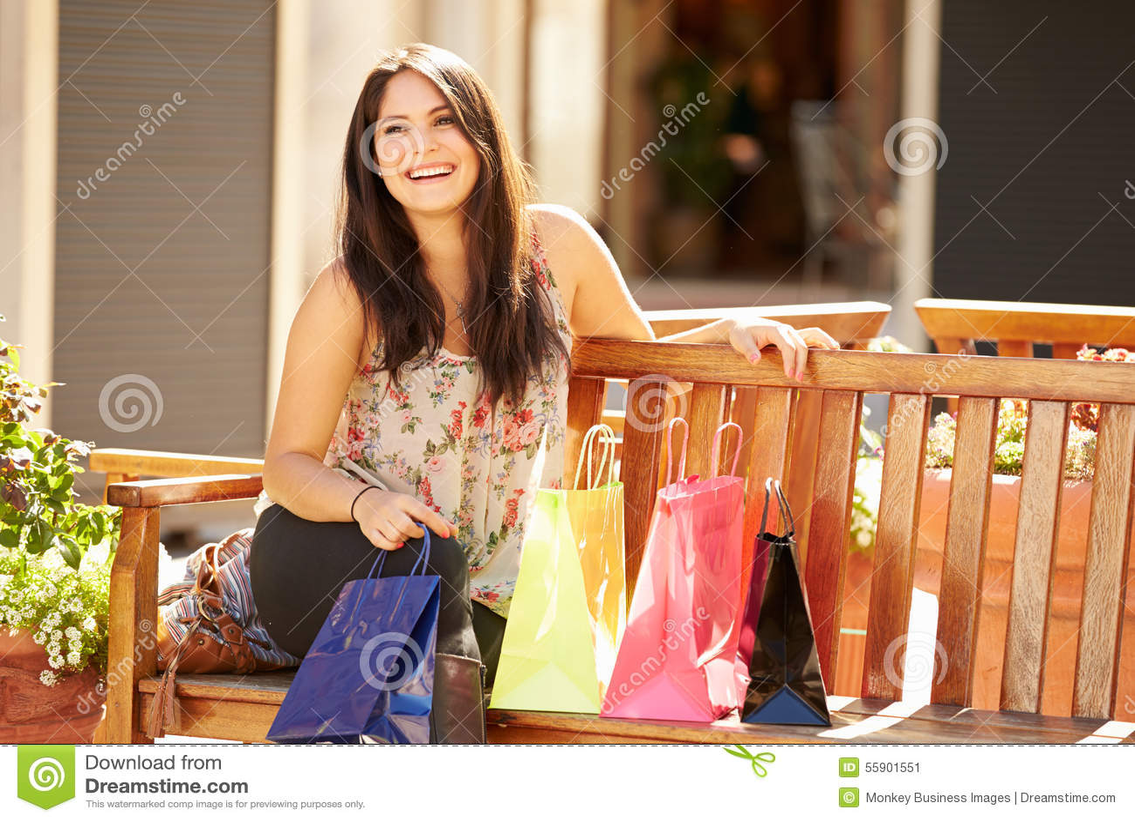 Kvinna som vilar med shoppingpåsar som sitter i galleria
