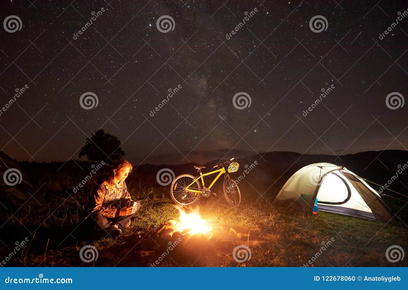 Kvinna som vilar på natten som mycket campar nära lägereld, turist- tält, cykel under aftonhimmel av stjärnor