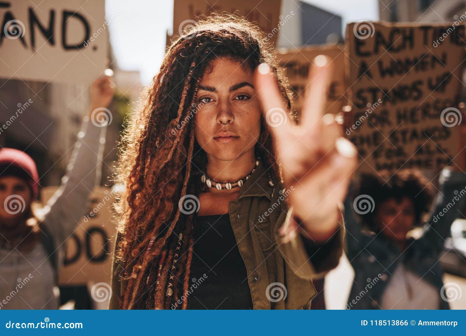 Kvinna som visar ett fredtecken under protest
