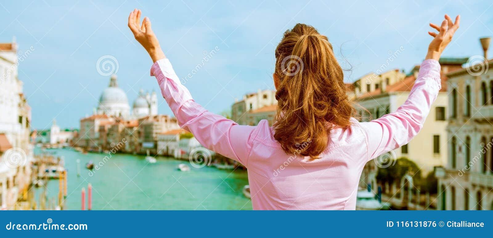 Kvinnaanseende på bron med sikt för storslagen kanal i ve