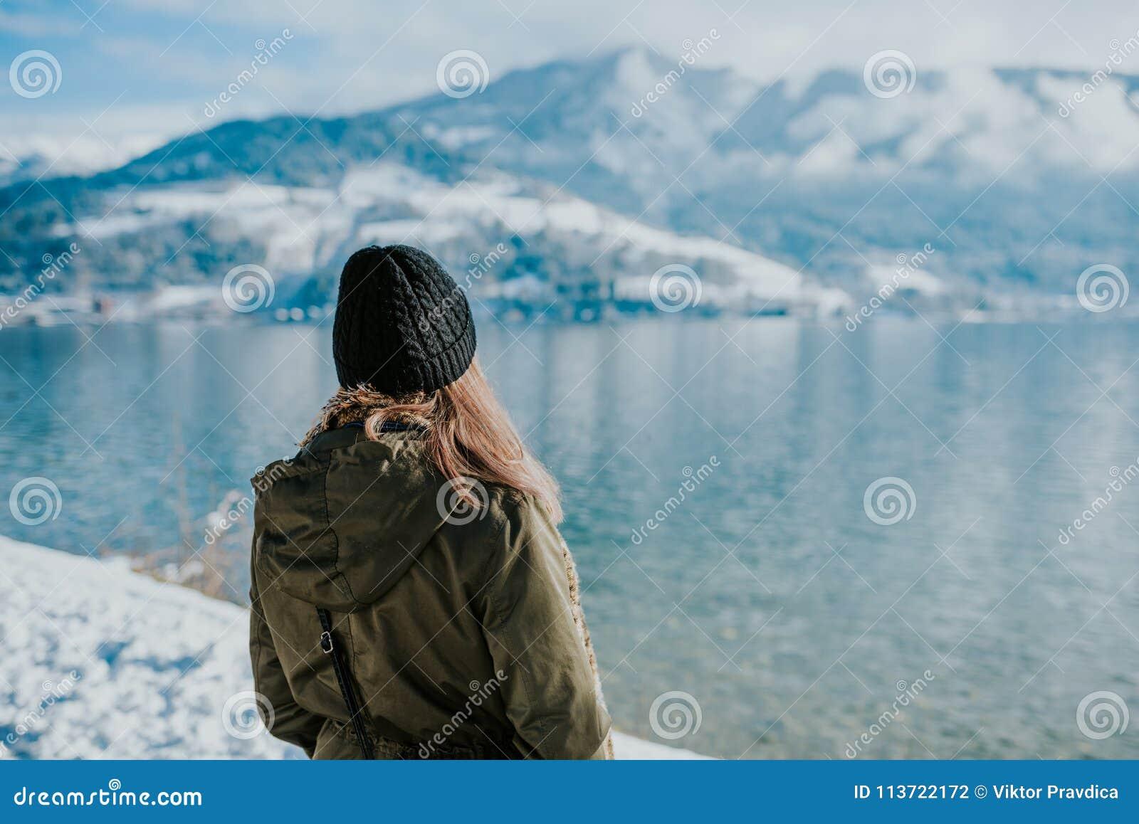 Kvinnaanseende på lakeshore med snöig berg i baksidan