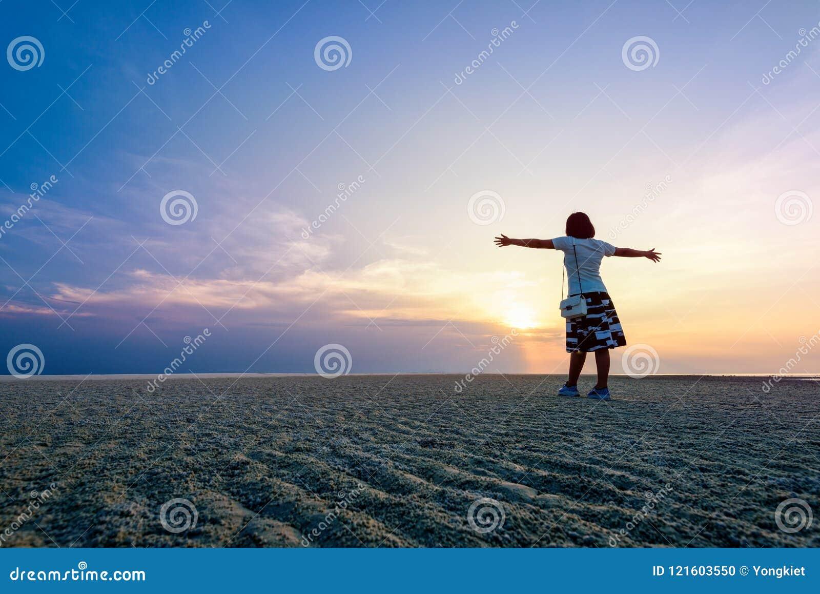 Kvinnaanseendet beväpnar utsträckt på solnedgången