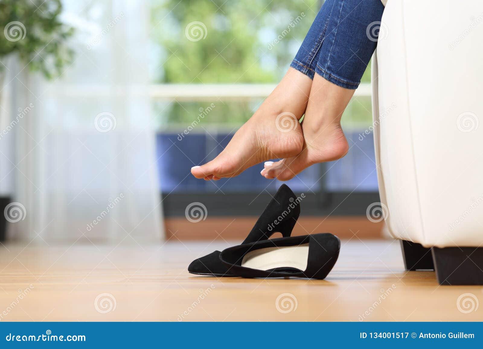 Kvinnaben och skor som hemma vilar på en soffa