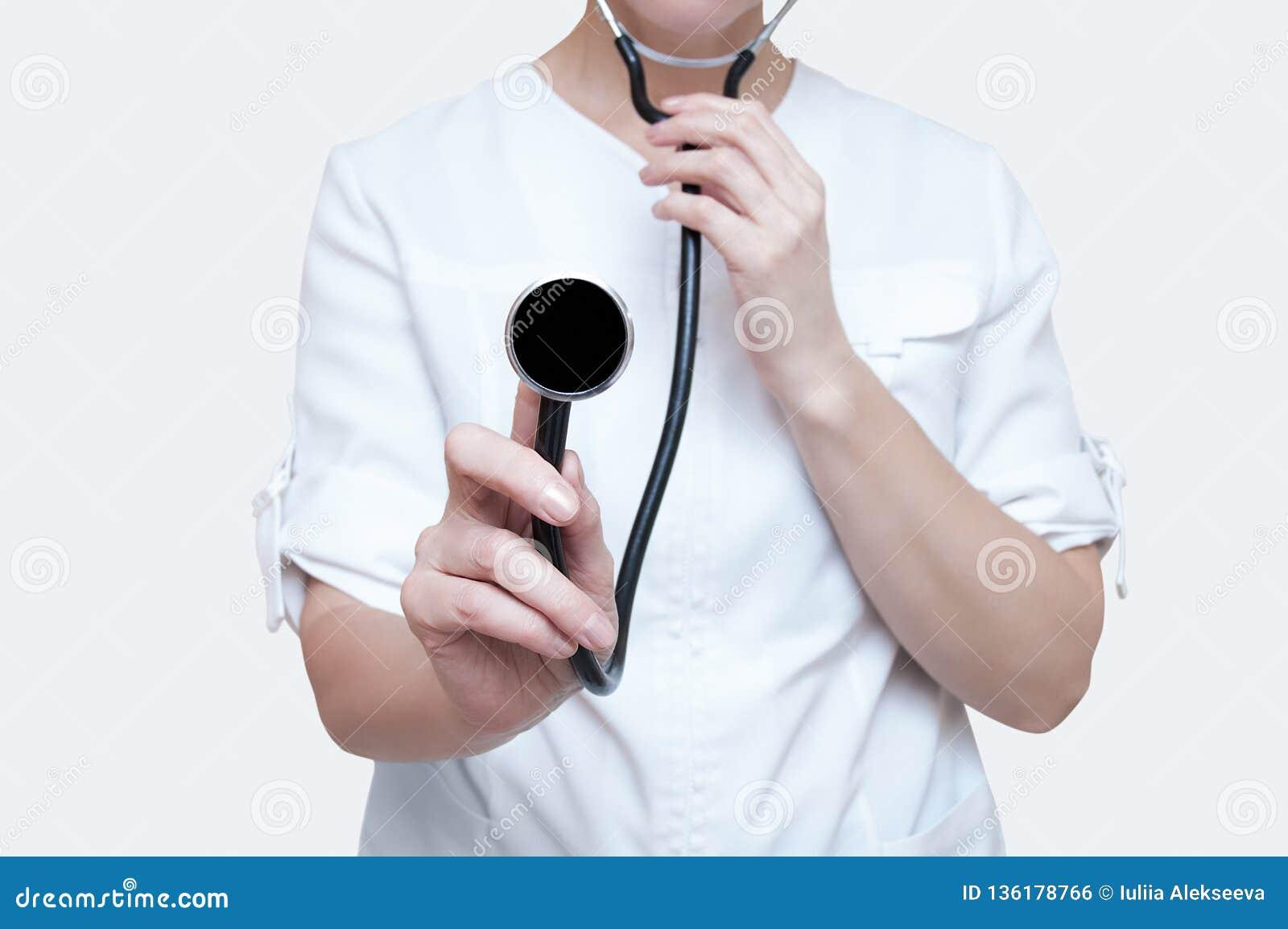 Kvinnadoktor med en stetoskop i händer på vit bakgrund isolate