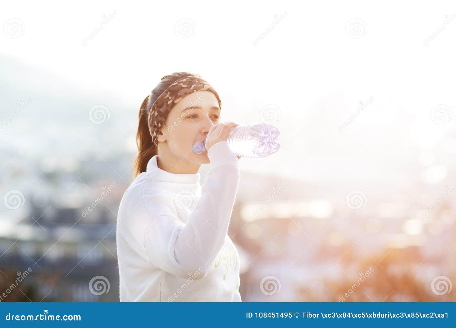 Kvinnadricksvatten under en spring Höst Kallt väder Jogga kvinnan i en stad under en vinter solig dag Dricka funktionsläge