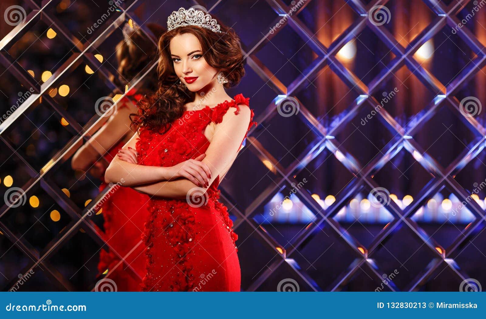 Kvinnadrottningprinsessan i kronan och luxklänningen, ljus festar backgr
