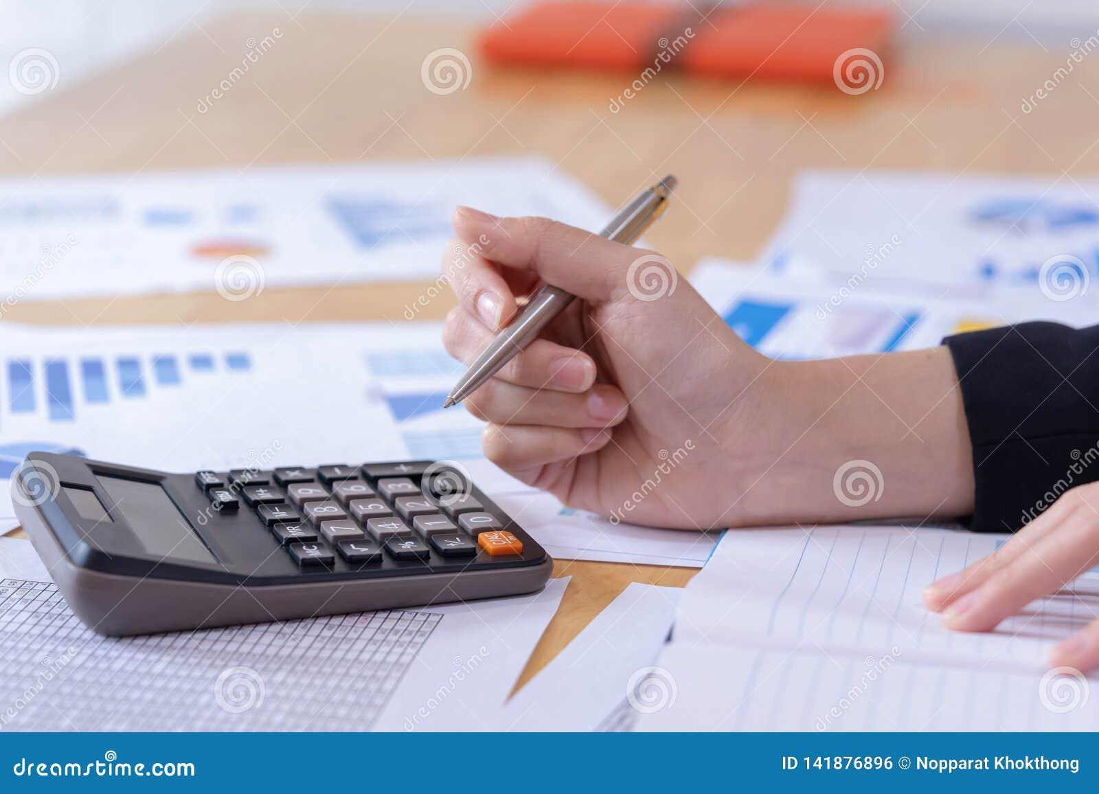 Kvinnaentreprenör som använder en räknemaskin till beräkning av finansiell kostnad på kontoret