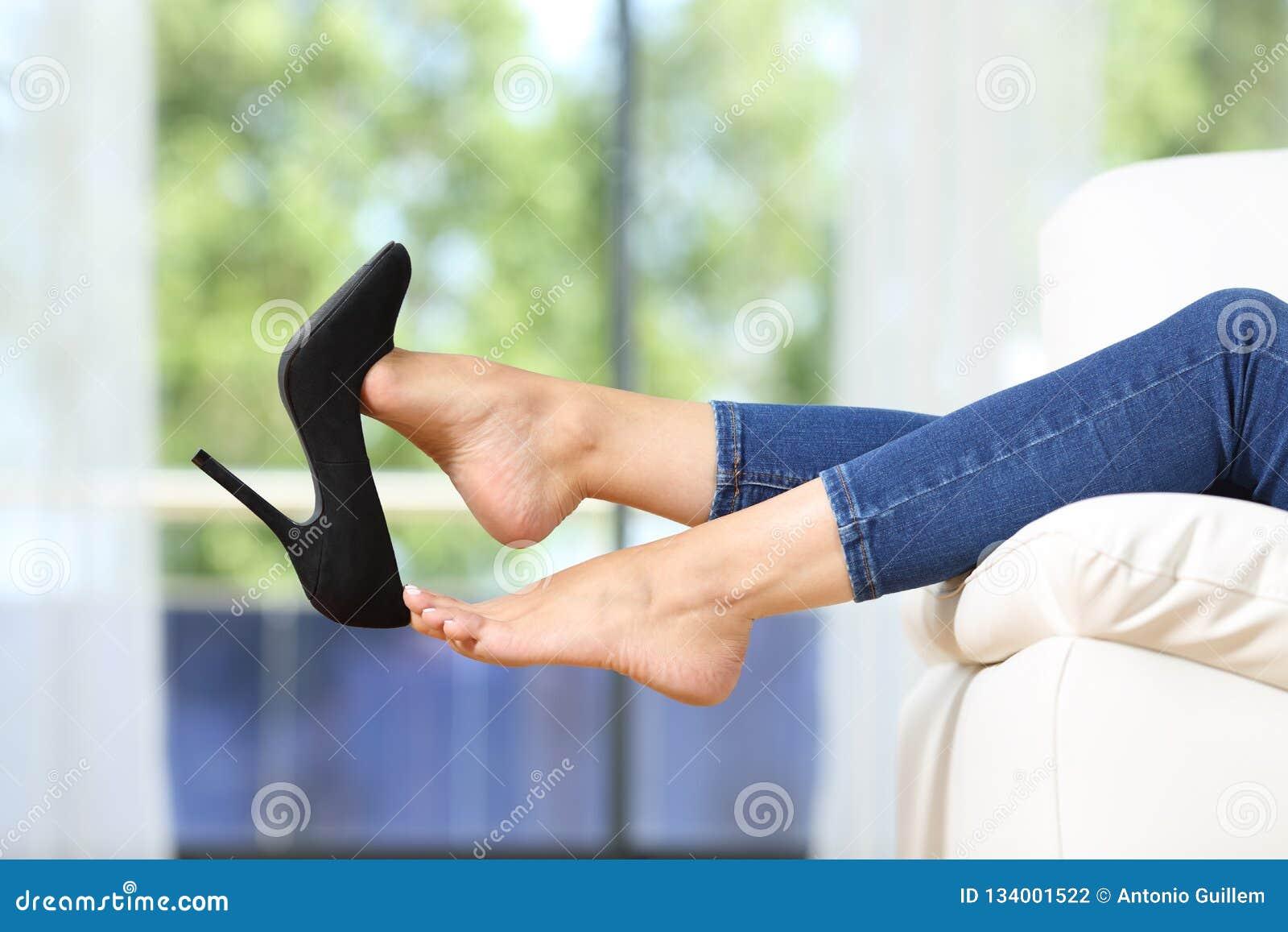 Kvinnafoten som tar av, skor att vila på en soffa