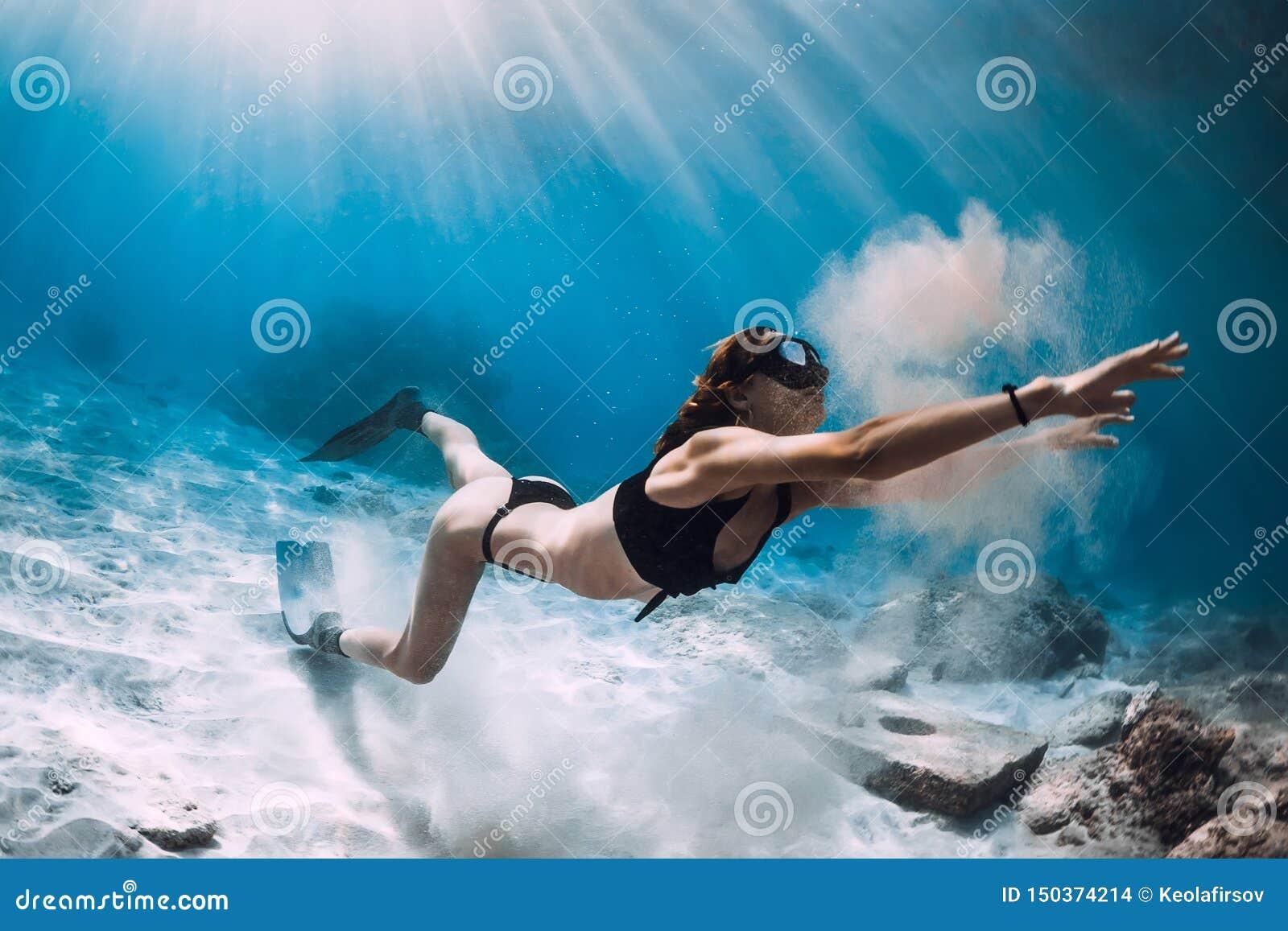 Kvinnafreediver med sand ?ver det sandiga havet med fena Freediving i den hawaianska ön