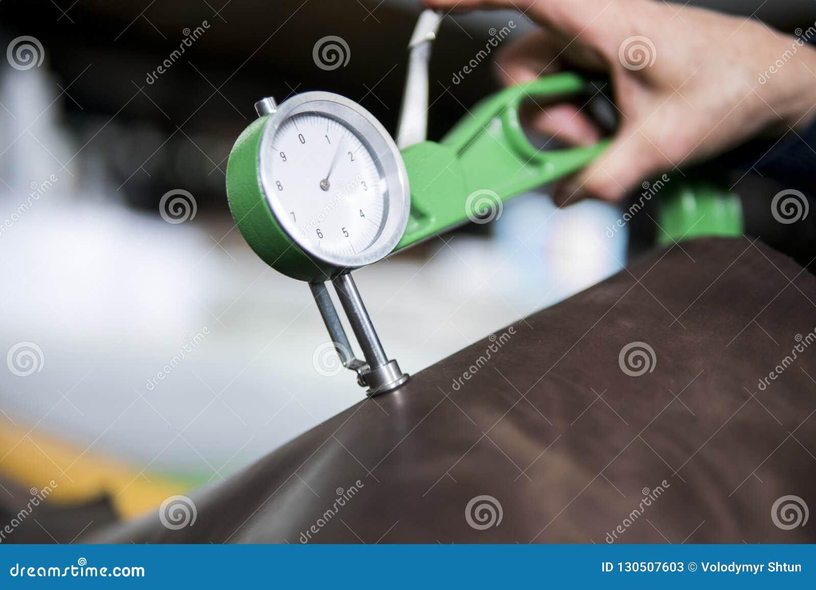 Kvinnahänder använder på lädertjockleksmåttet med ett naturligt brunt läder Förbereda sig av råvarorna för tillverkning