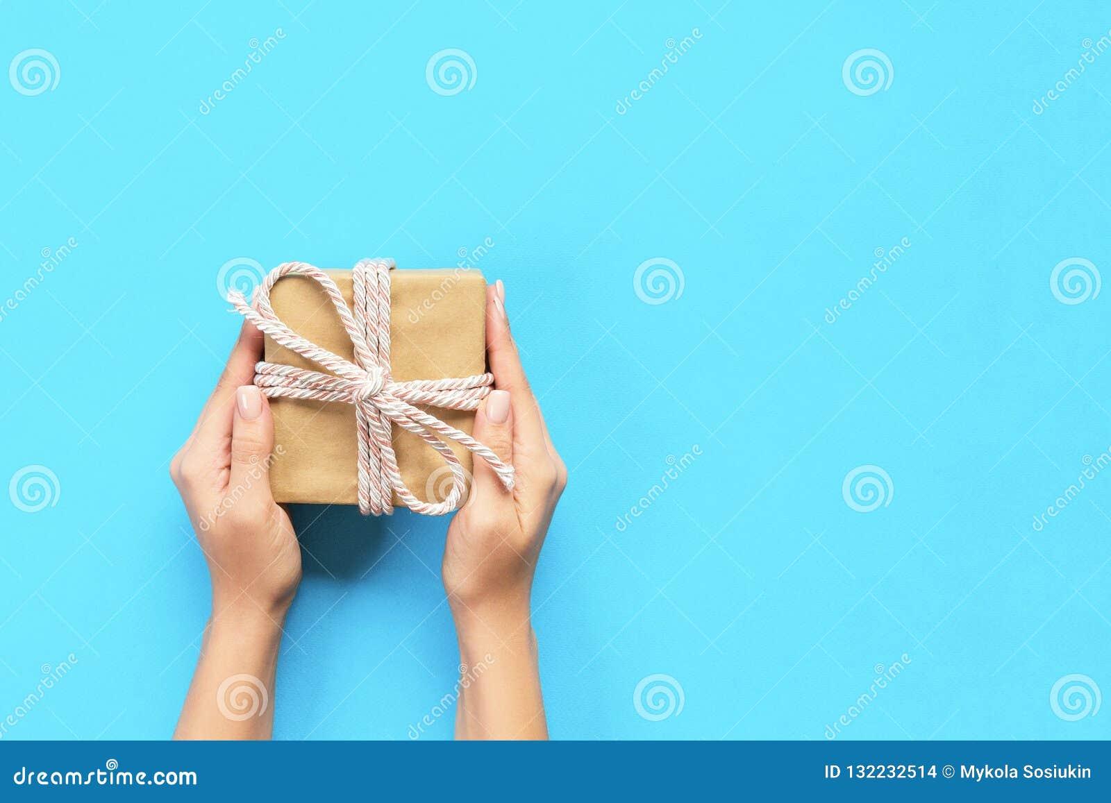 Kvinnahänder ger den slågna in valentin eller annan ferie handgjord gåva i papper med strumpebandsorden Närvarande ask, garnering