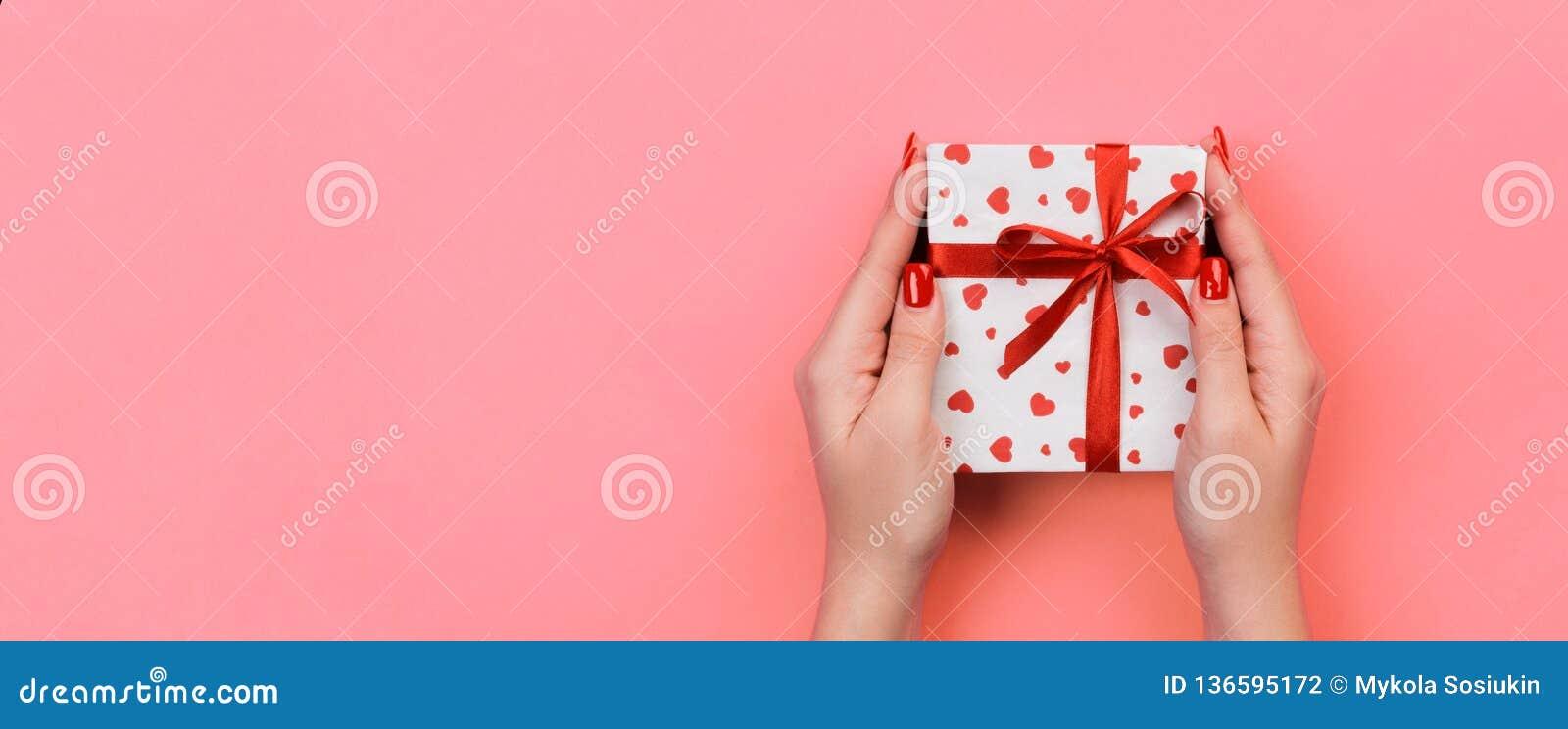 Kvinnahänder ger valentin eller annan ferie handgjord gåva i papper med det röda bandet Närvarande ask, röd hjärtagarnering av gå