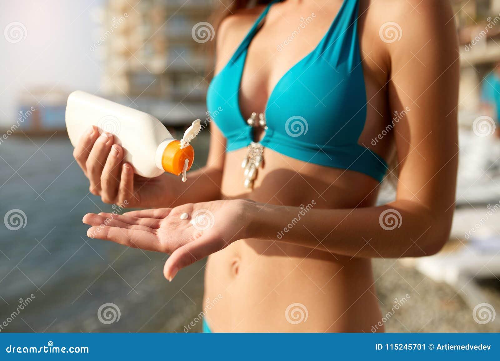 Kvinnahänder som sätter sunscreen från en solbrännakrämflaska Caucasian kvinnlig åtstramningsuncream på hennes hand garvad flicka