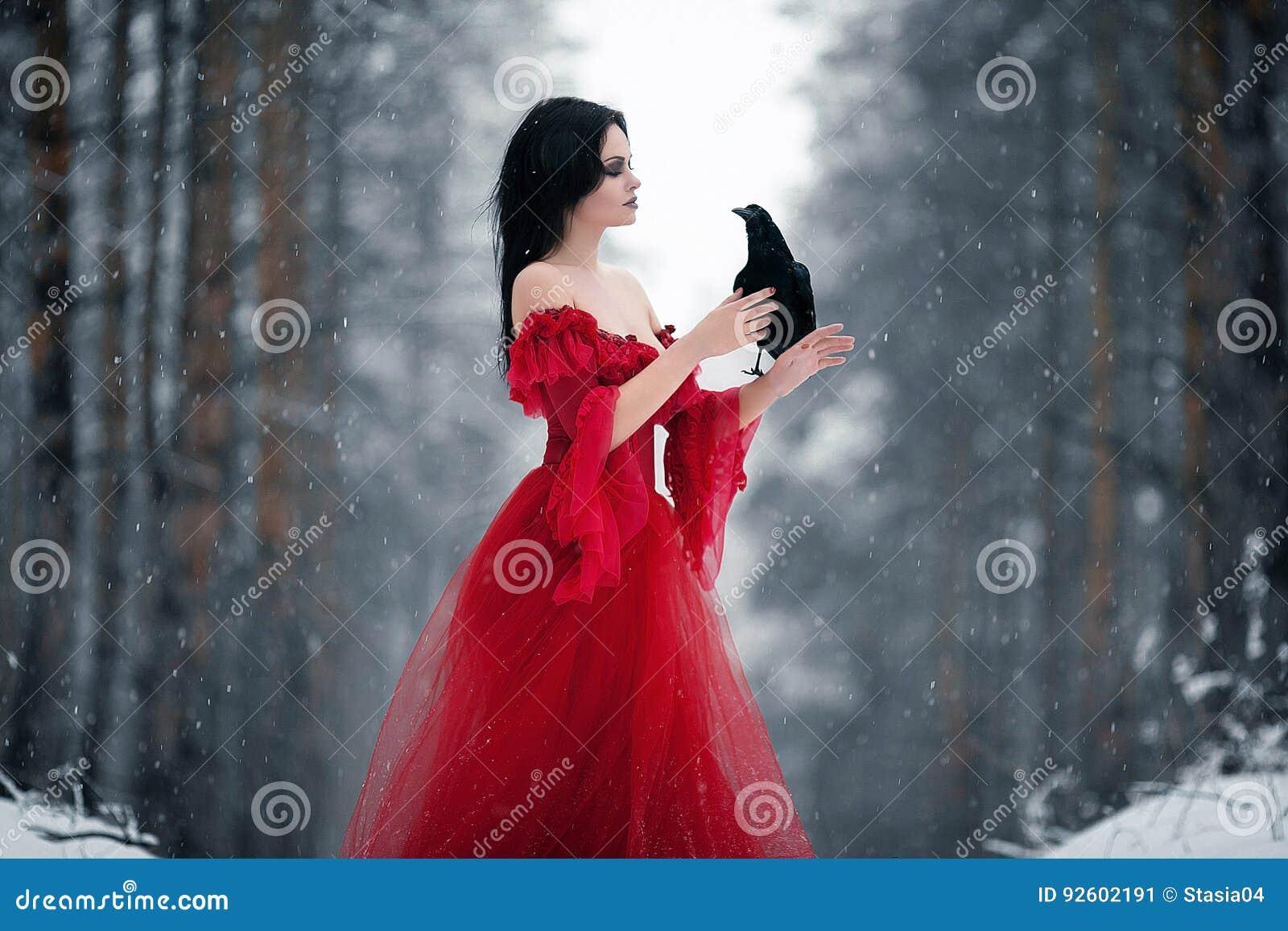 Kvinnahäxa i röd klänning och med korpsvart i hennes händer i snöig fo