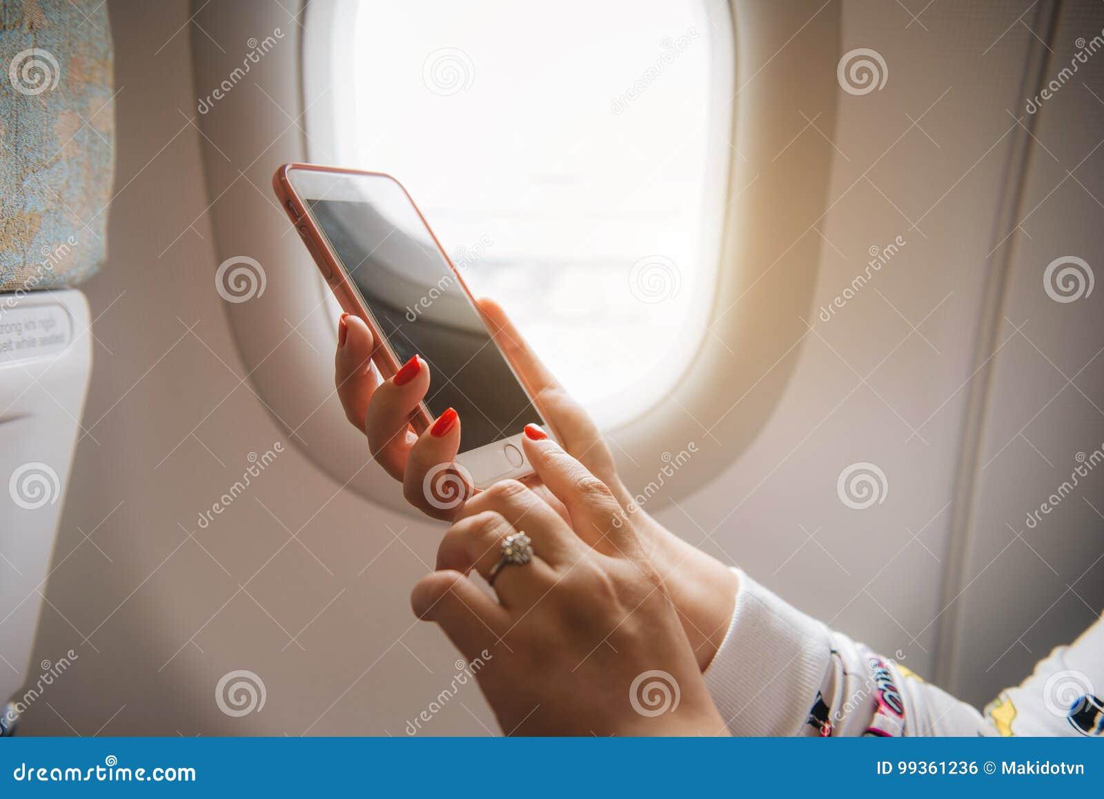 Kvinnahand genom att använda den smarta telefonen på flygplanet Kvinnligt använda för handelsresande