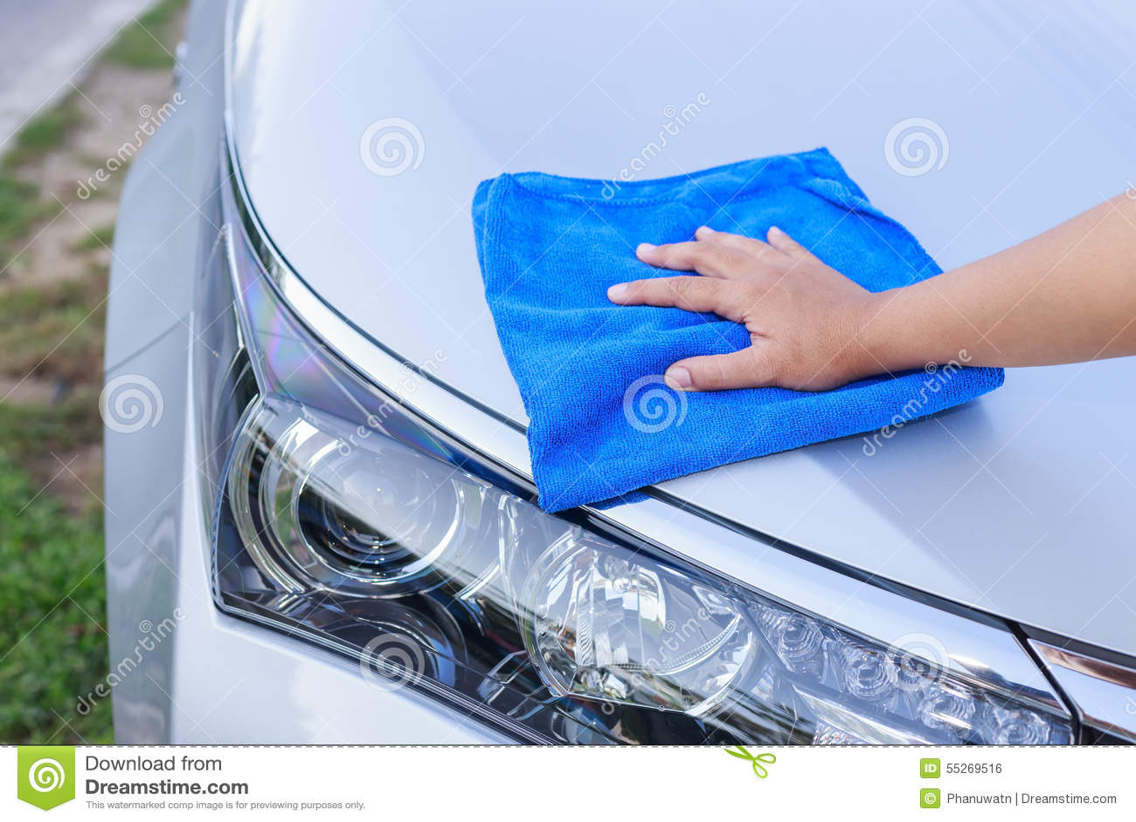 Kvinnahand med den blåa microfibertorkduken som gör ren bilen