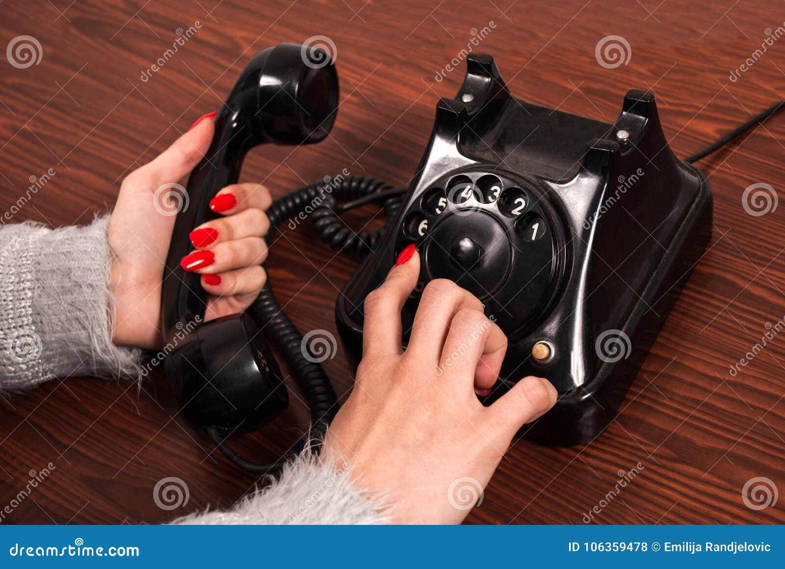Kvinnahand och gammal telefon på träskrivbordet Fingervisartavlatelefonnummer