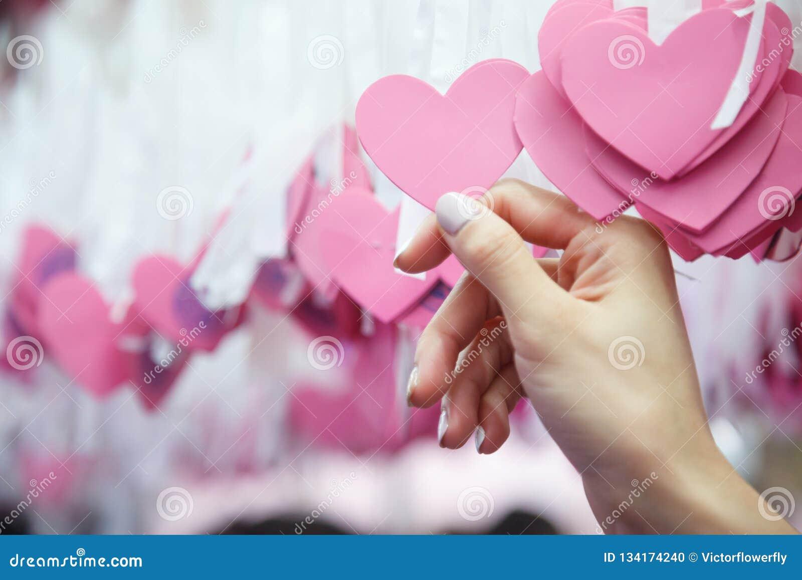 Kvinnahand - rosa hjärtaform Lucky Draw som för hacka fästas till det vita bandet på att önska trädet i välgörenhethändelse Lekar