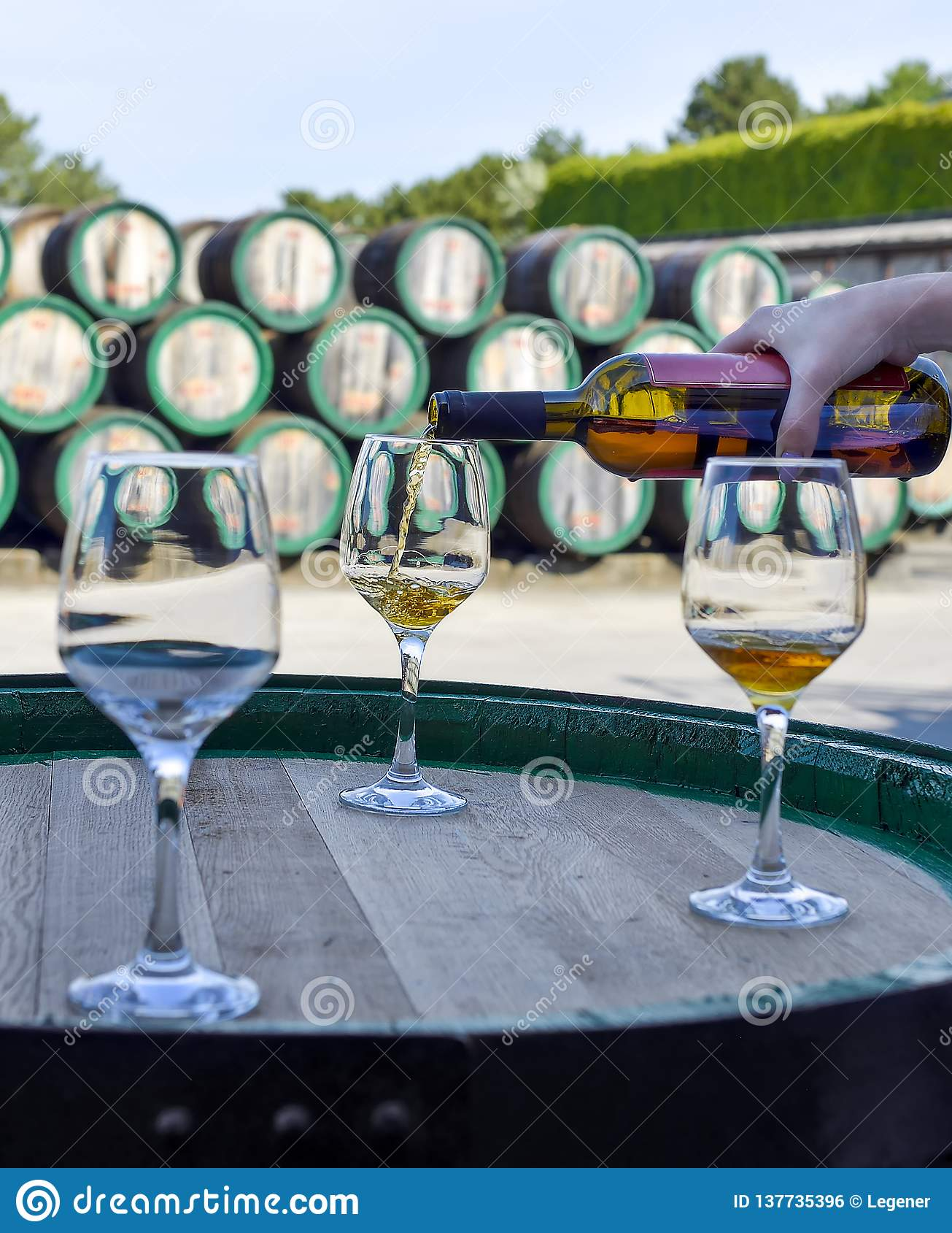 Kvinnahand som häller guld- vin från flaskan in i exponeringsglas
