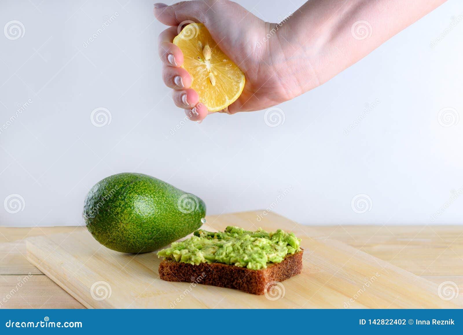 Kvinnahand som till h?lften pressar av citronen p? avokadorostat br?d f?r helt br?d