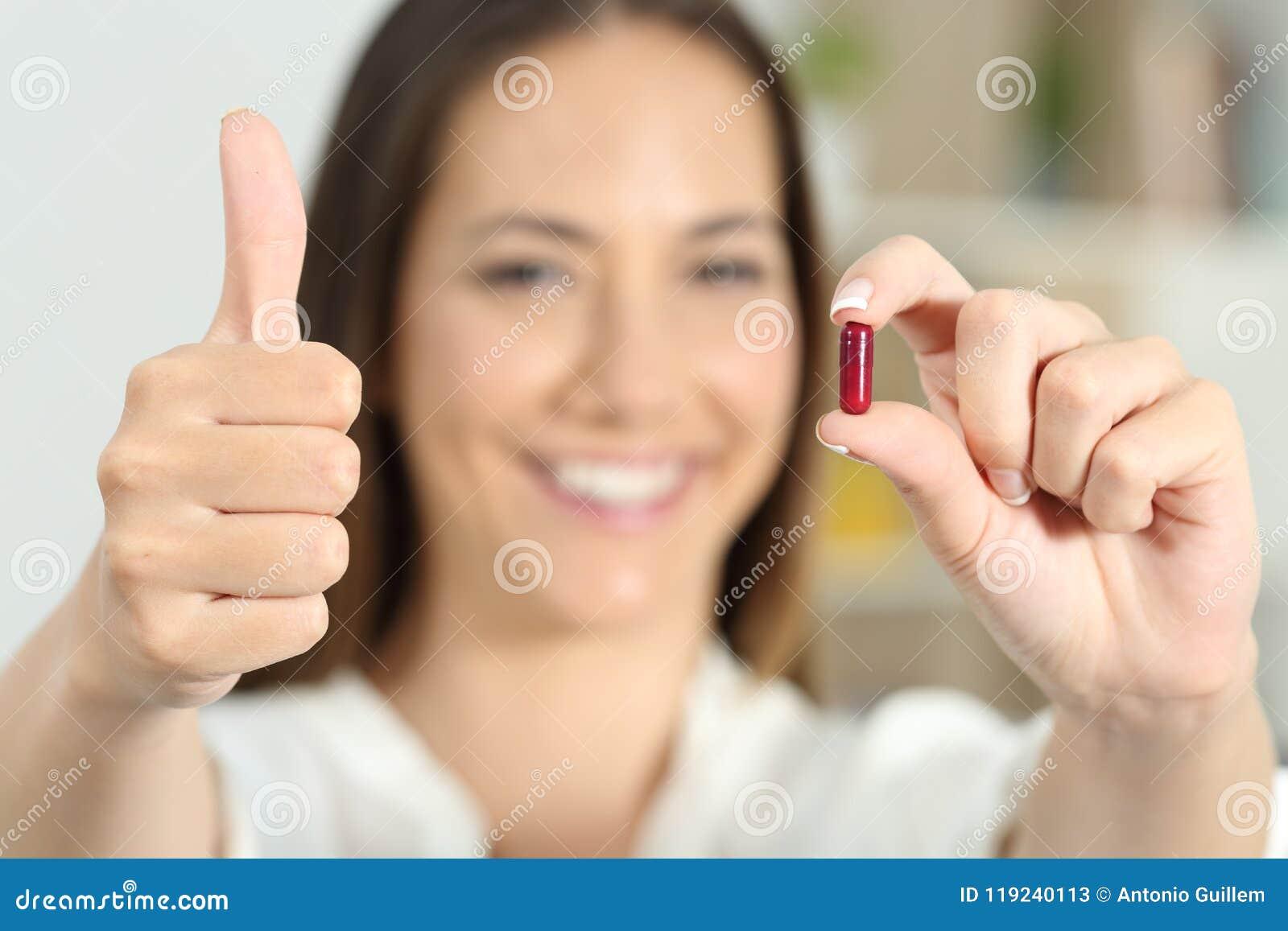 Kvinnahand som visar en medicinkapsel med tummar upp