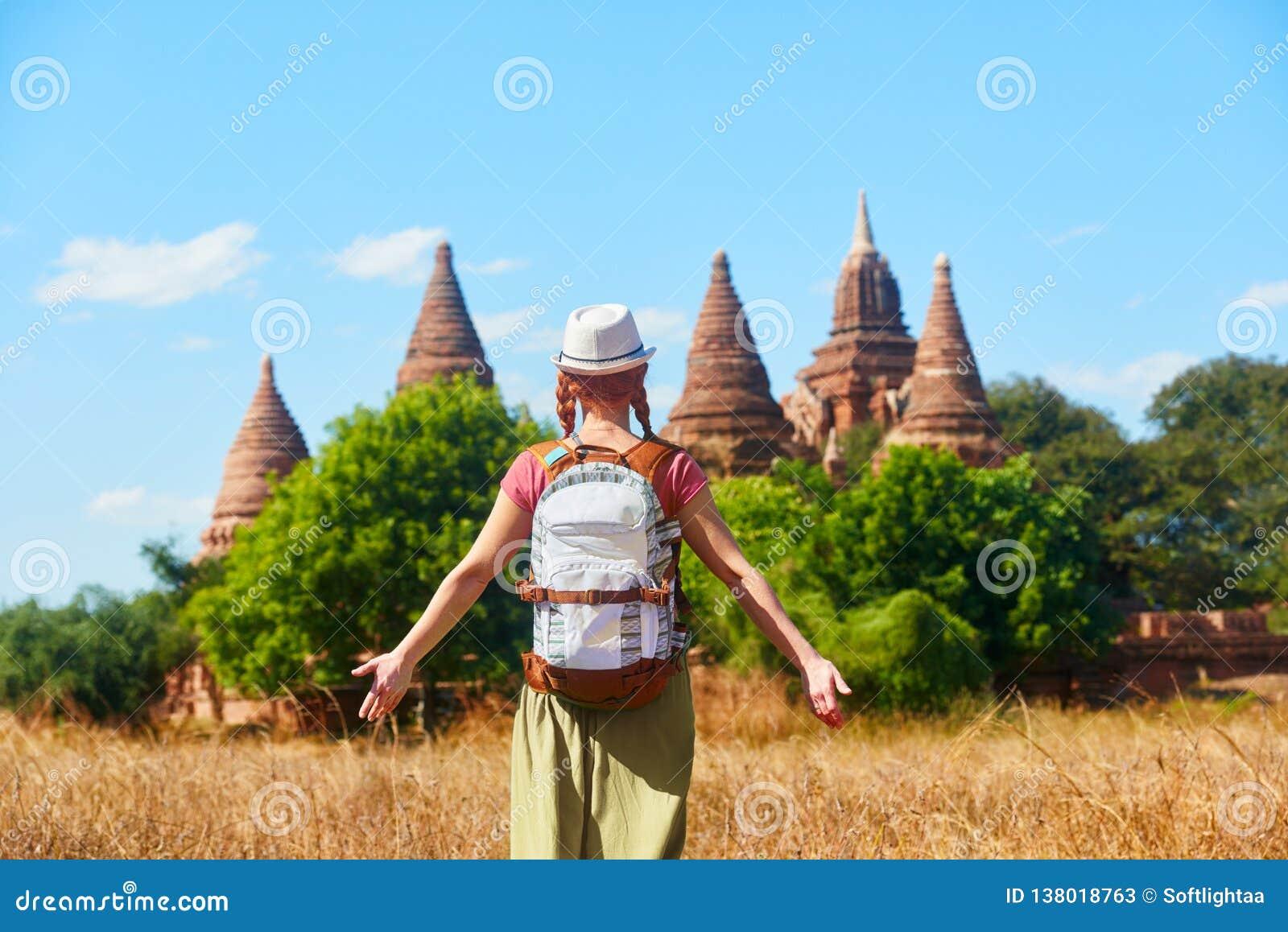 Kvinnahandelsresande med en ryggsäck som går till och med fält till forntida stupas