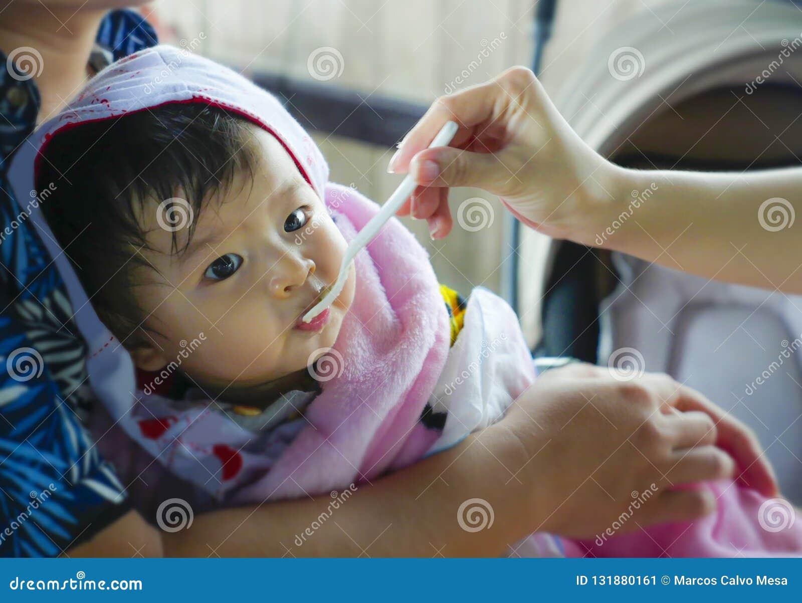 Kvinnahanden med skeden som matar hennes dotter, en söt och förtjusande härlig asiatisk kines, behandla som ett barn flickahållen