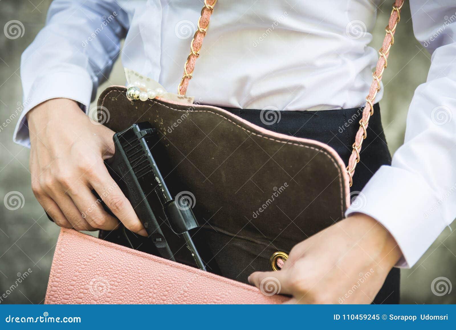 Kvinnahandinnehav som tar bort den lilla handeldvapnet från hennes handväska