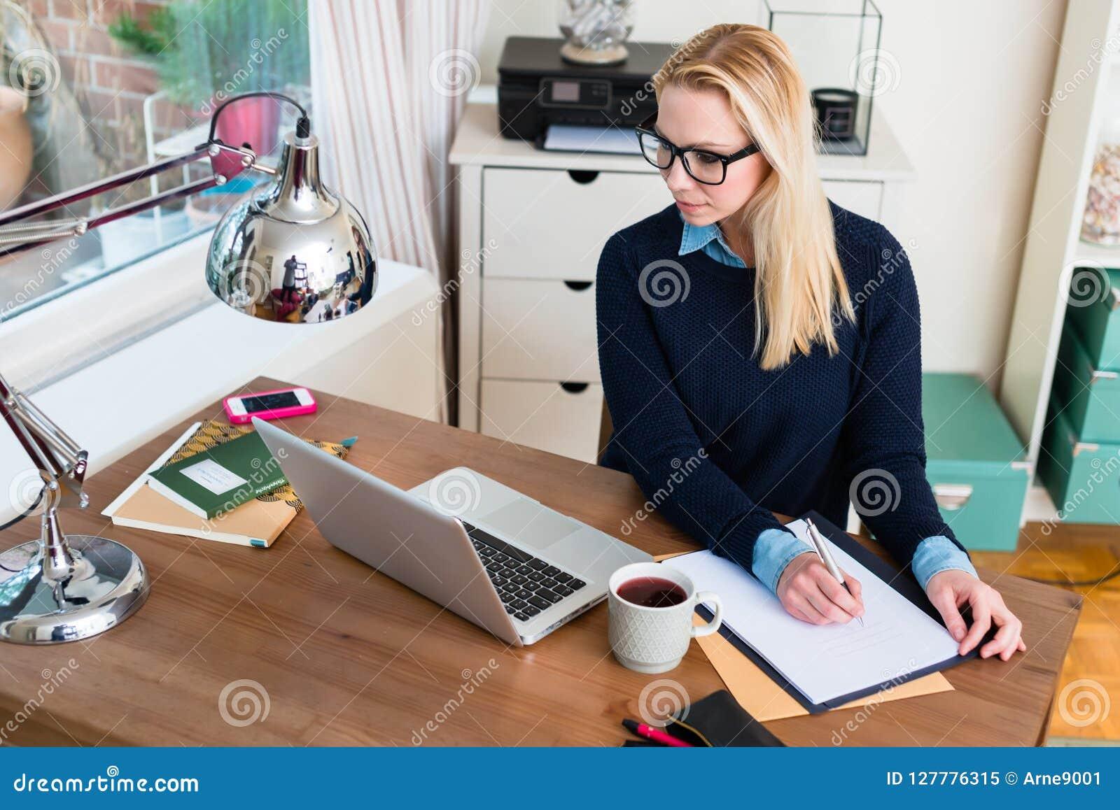 Kvinnahandstil på papper, medan se bärbara datorn