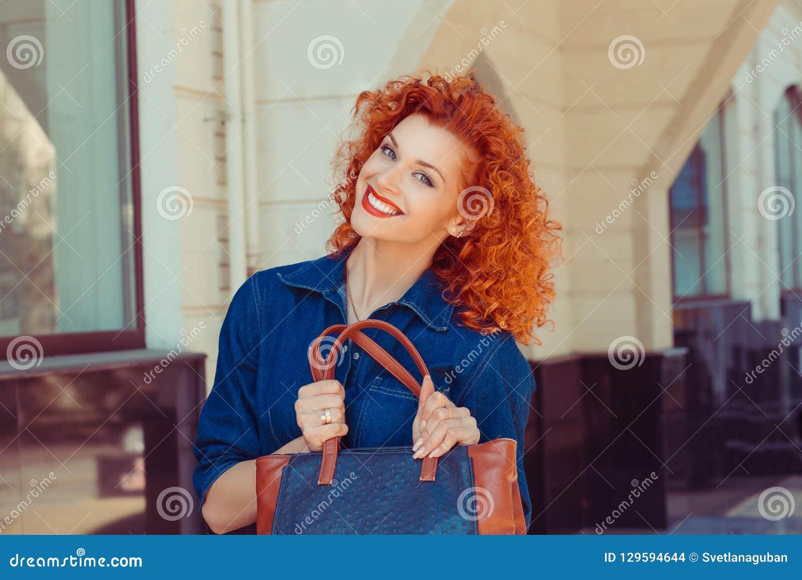 Kvinnainnehav som visar hennes nya påse för apelsinläderjeans