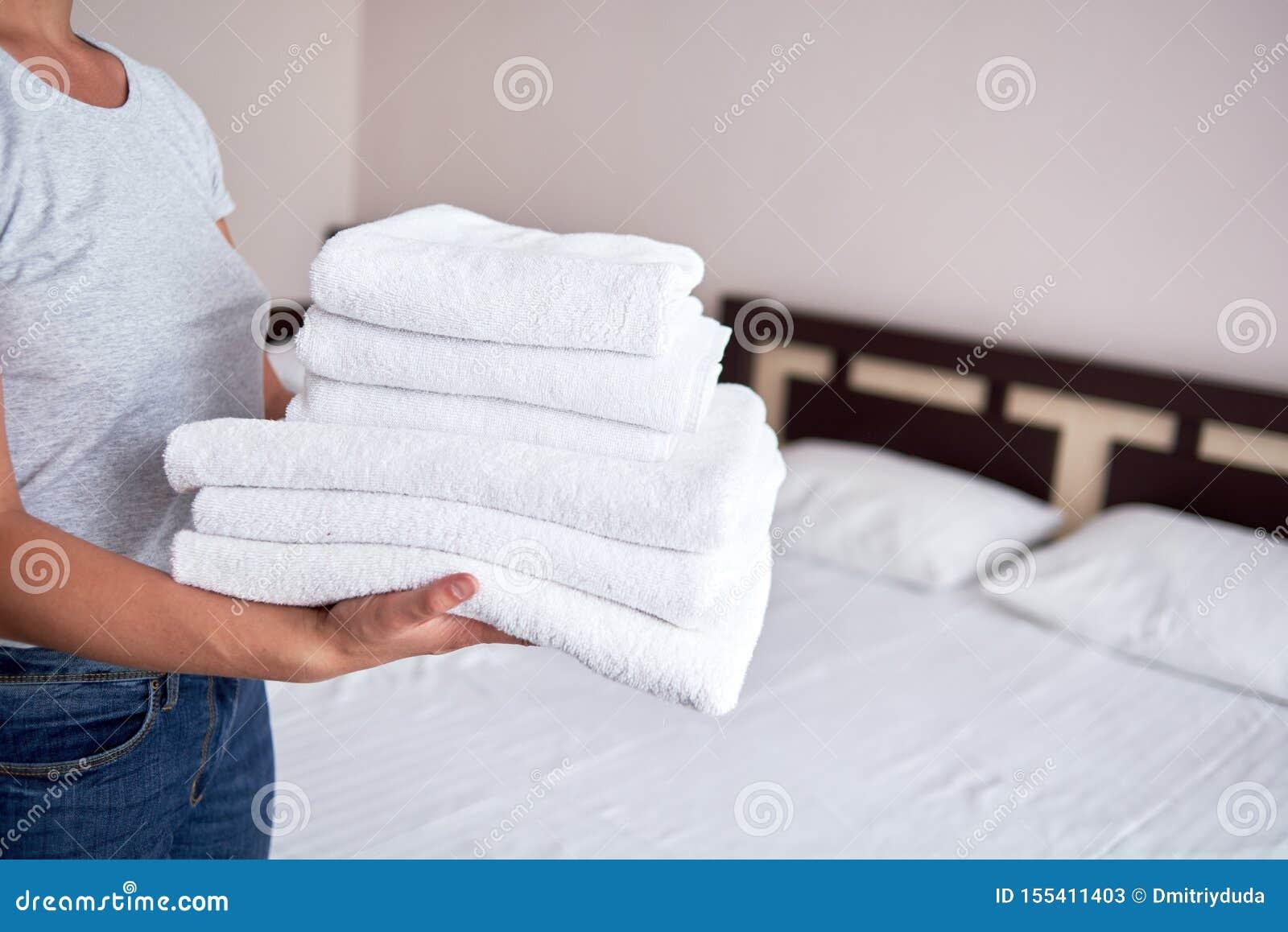 Kvinnainnehavbunt av vita rena badlakan i sovruminre, kopieringsutrymme Stäng sig upp händer av hotellhembiträdet med handdukar