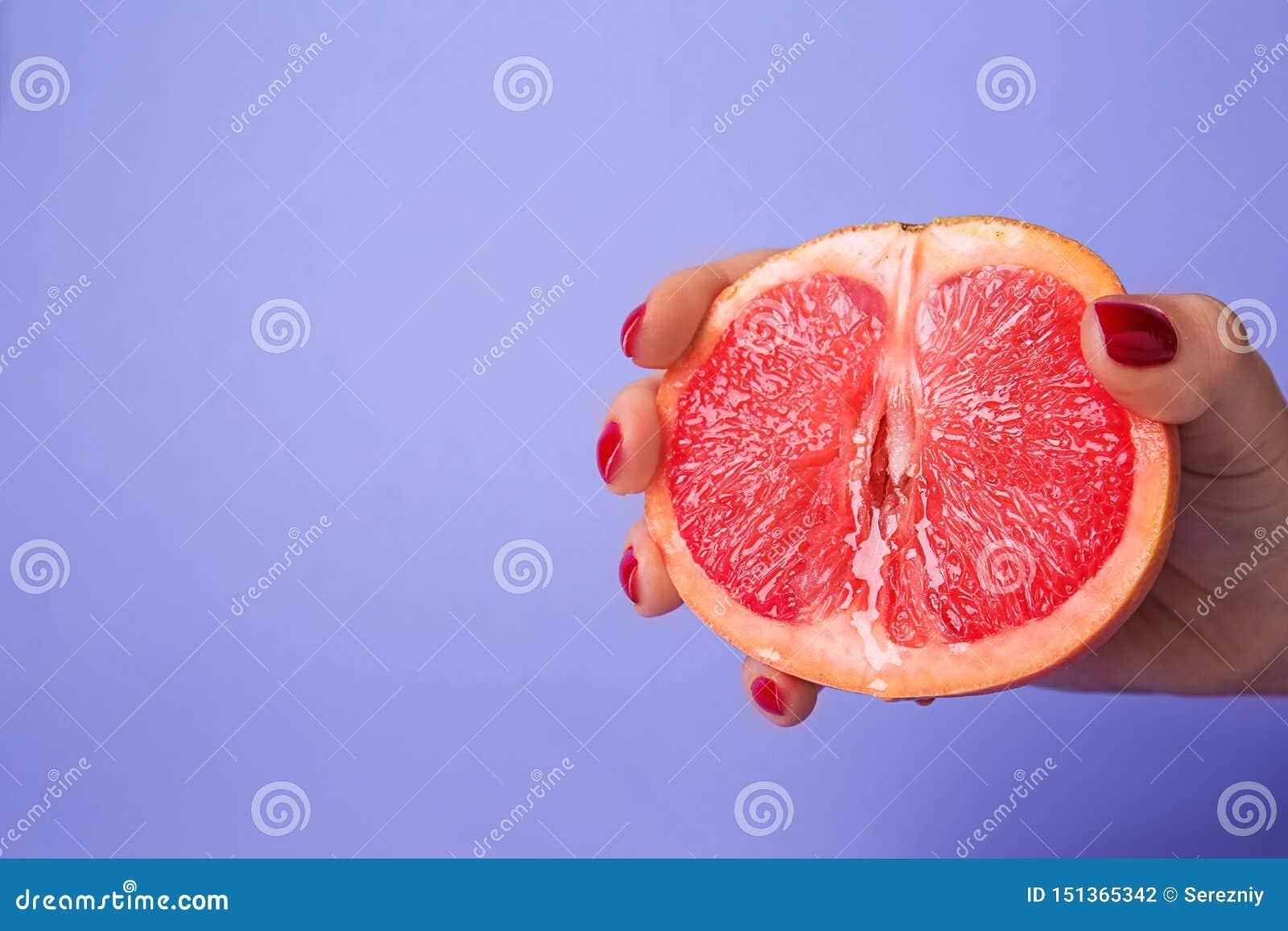 Kvinnainnehavhalva av den saftiga grapefrukten på färgbakgrund Erotiskt begrepp