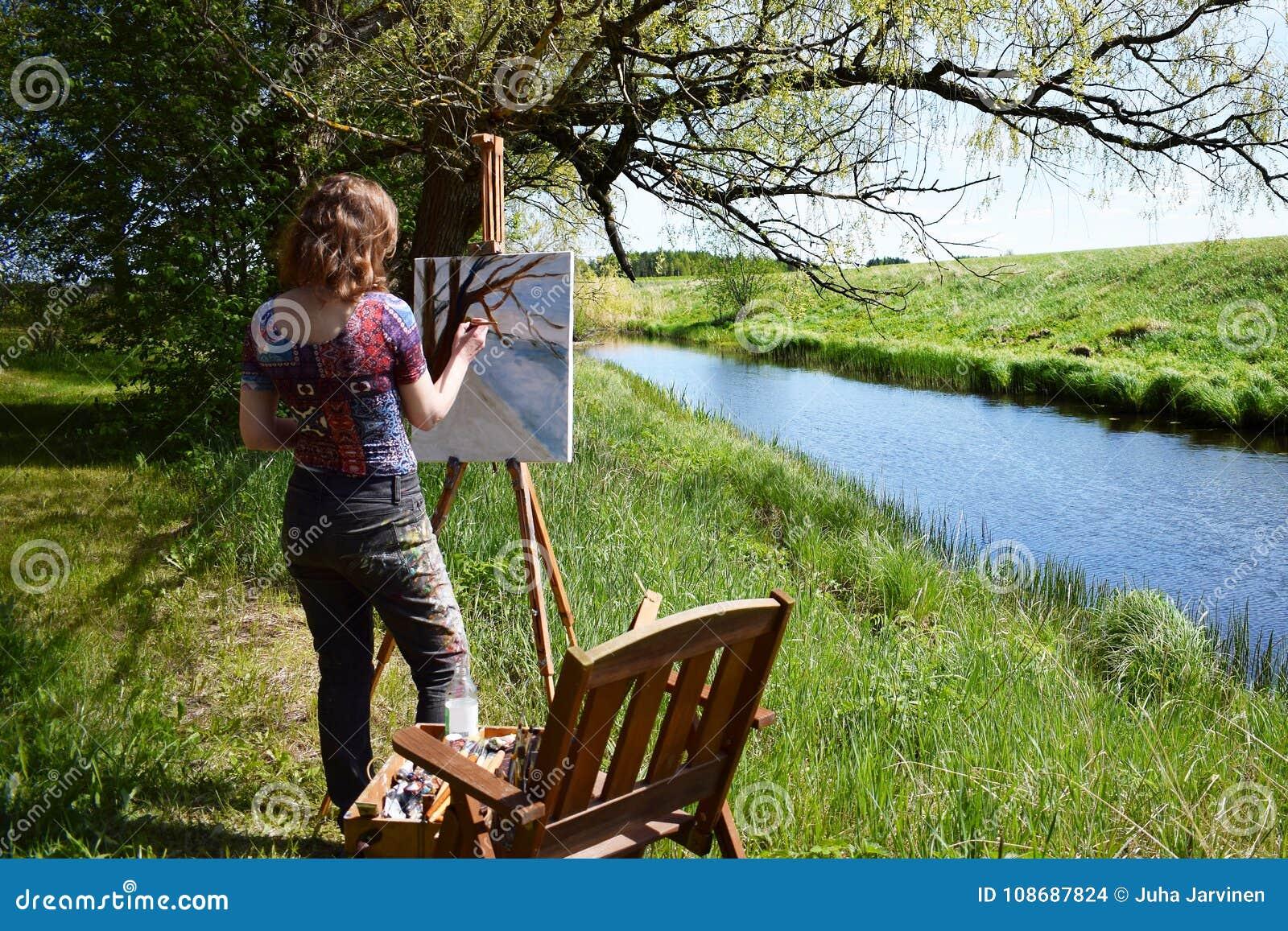 Kvinnakonstnären målar landskapmålning av den lilla floden