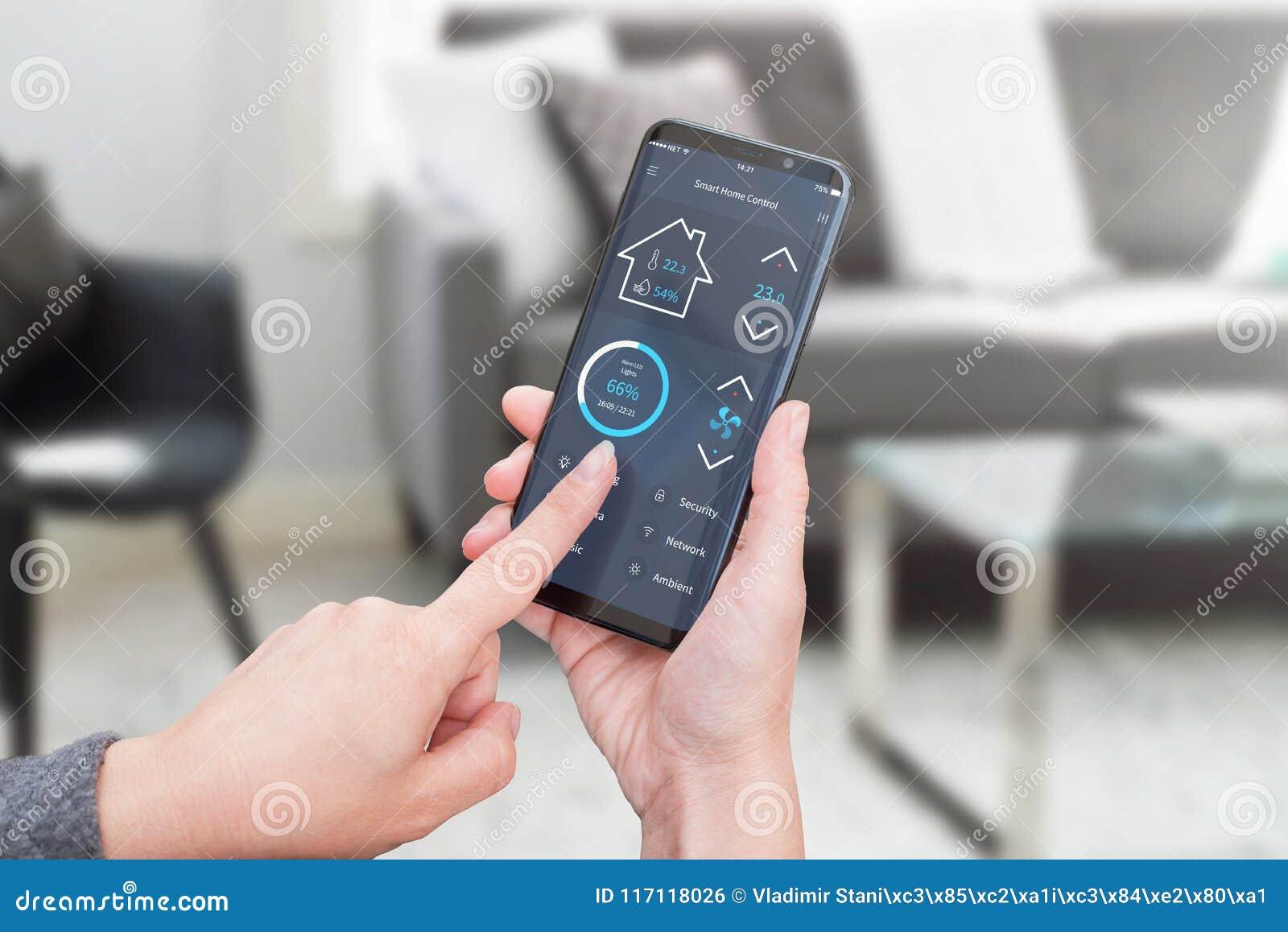 Kvinnakontrollljus i vardagsruminre med smart hem- kontroll app på moderna mobila enheter